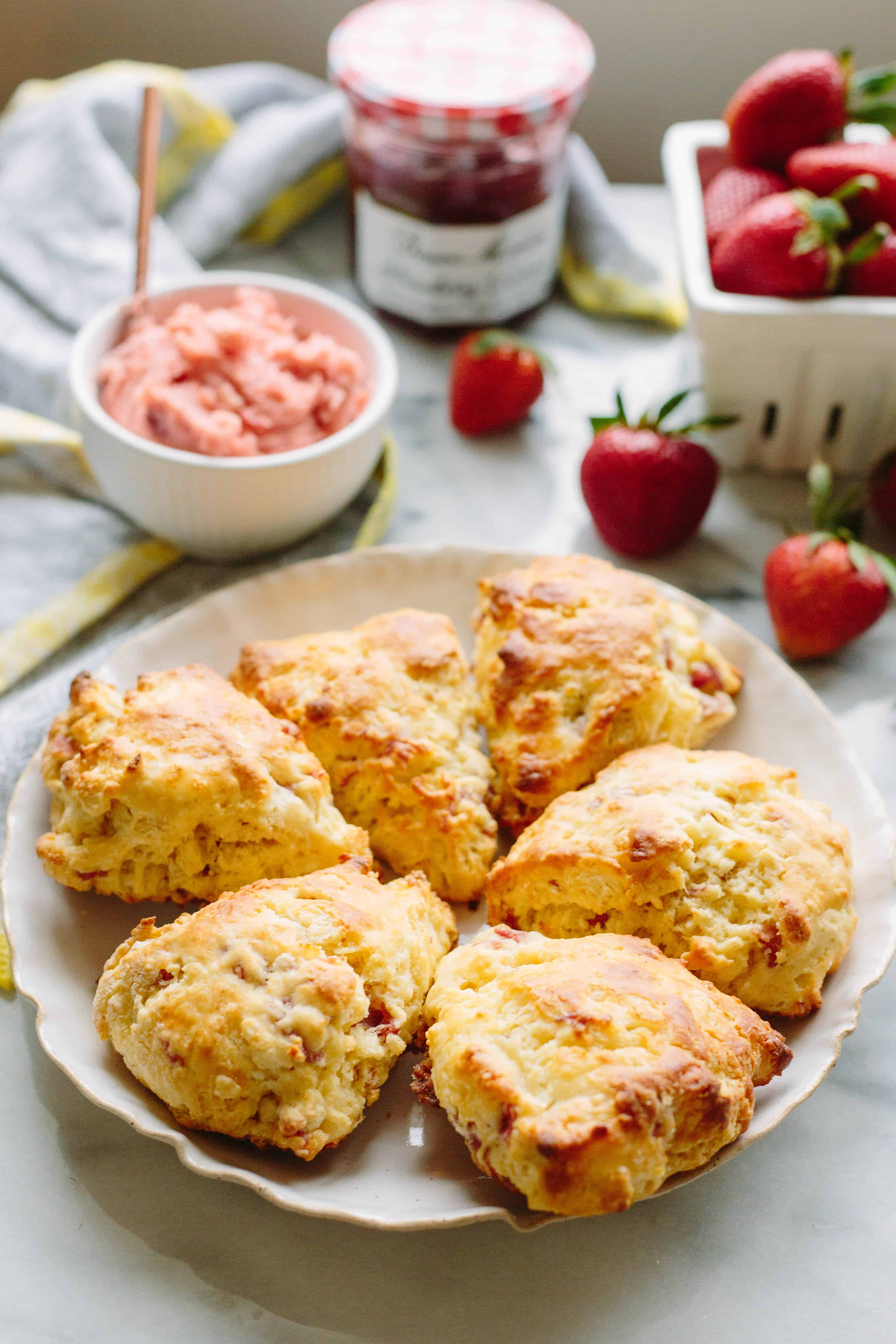 Six prosciutto goat cheese scones arranged in a circle on a white plate next to a bowl of strawberry butter.