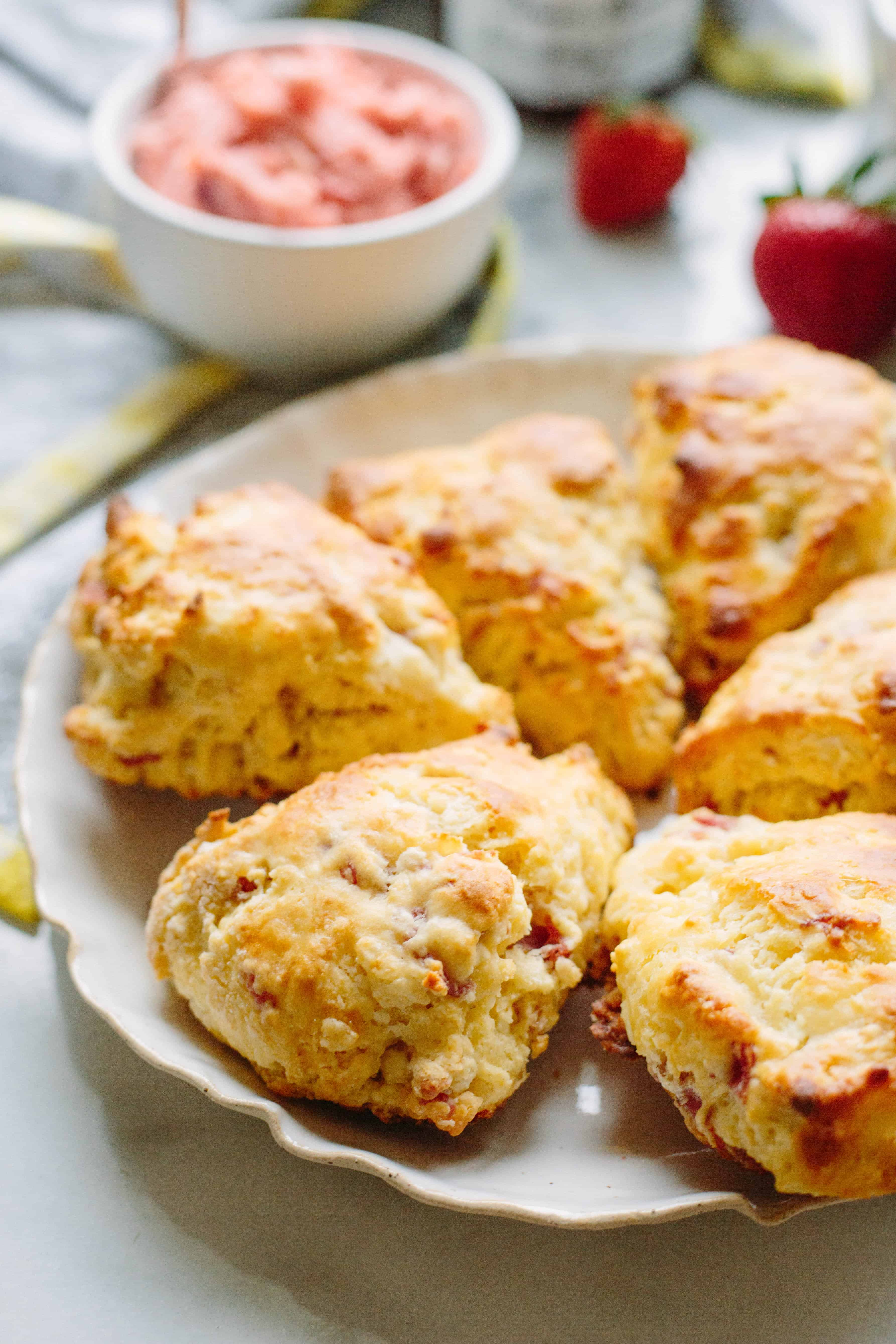 Prosciutto goat cheese scones arranged in a full circle on a white plate.