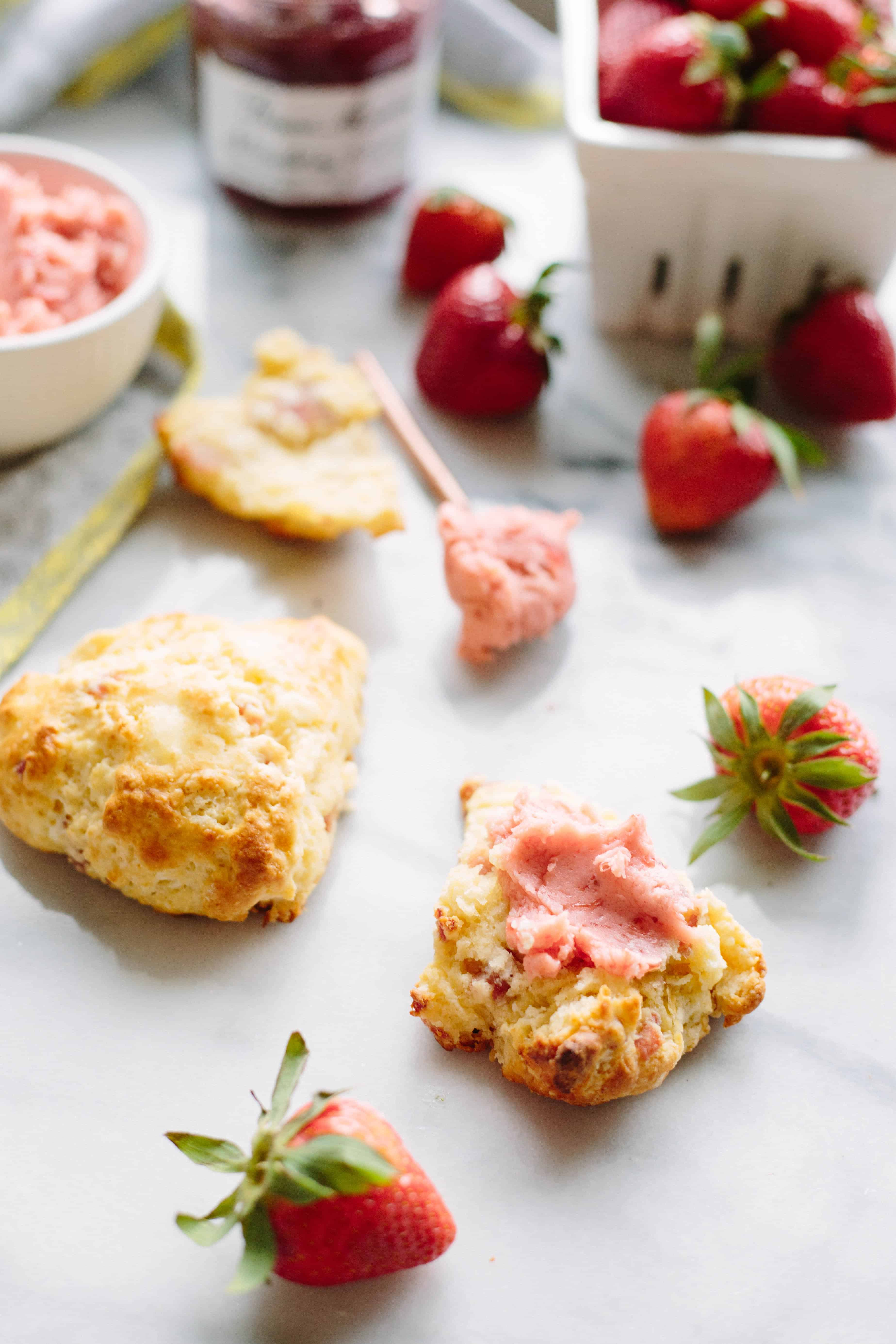 A split open scone spread with strawberry butter.