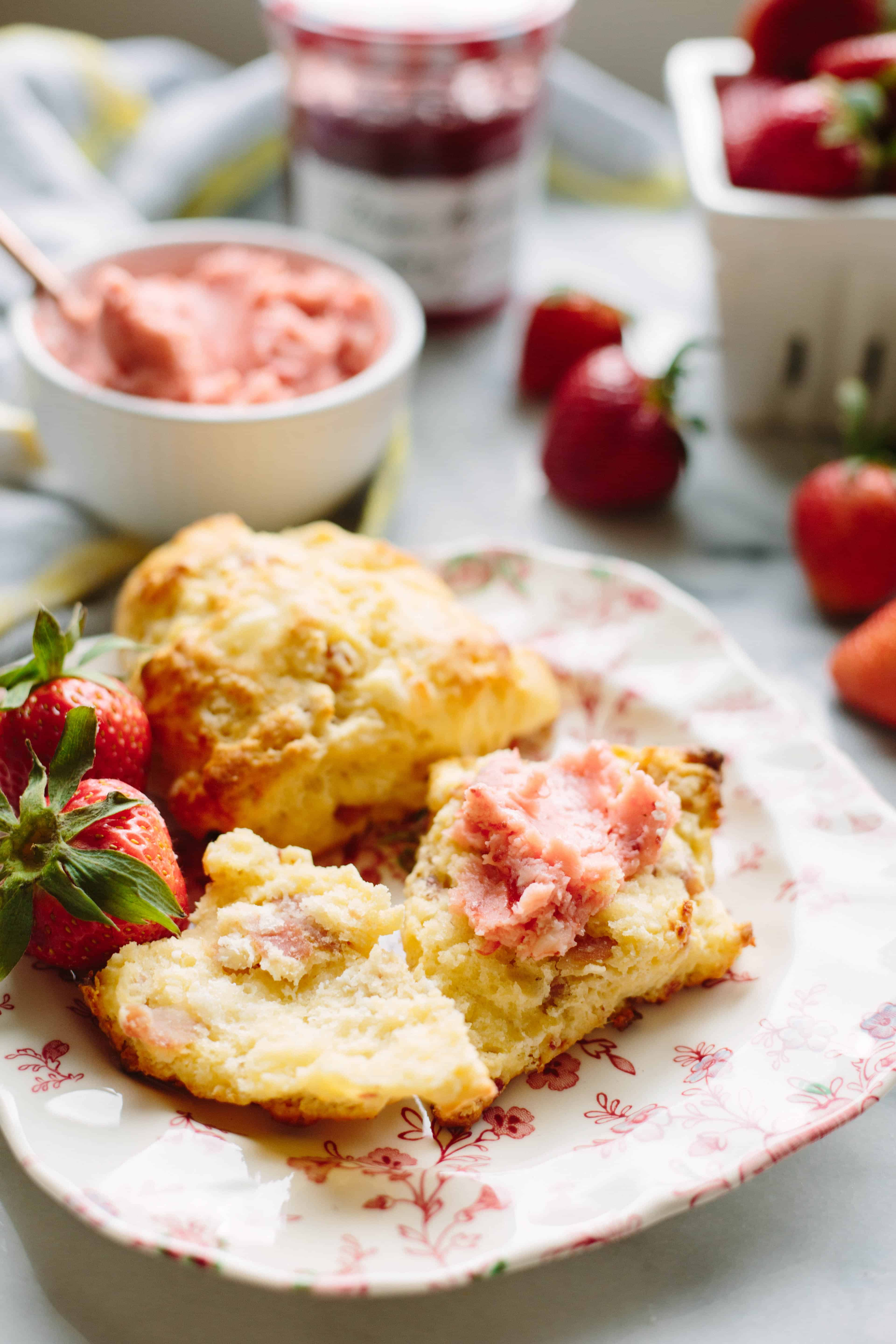 A whole scone and one split open and spread with butter on a small plate with whole strawberries.