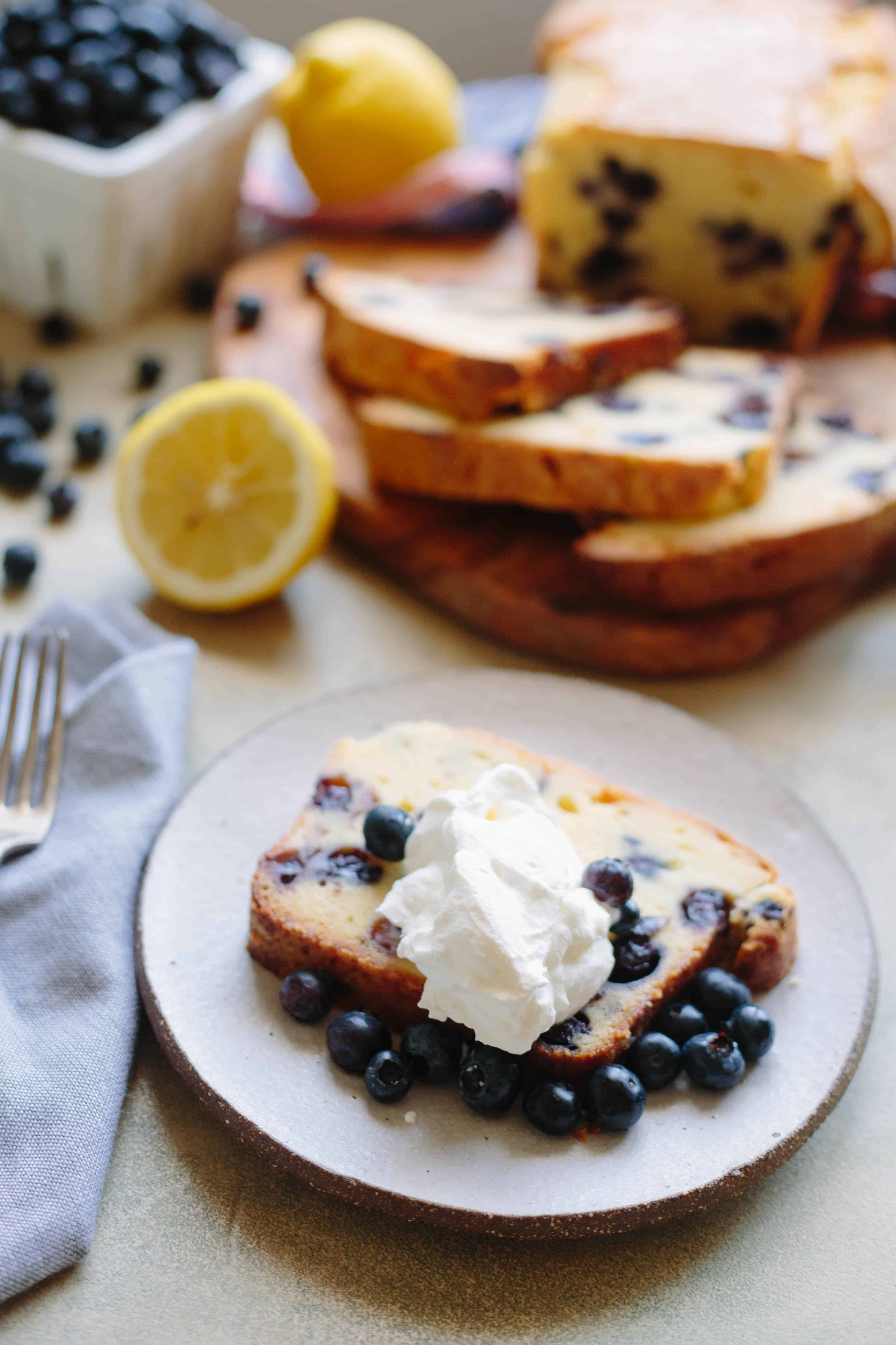 Slice of blueberry lemon pound cake with fresh blueberries and whipped cream on a dessert plate.