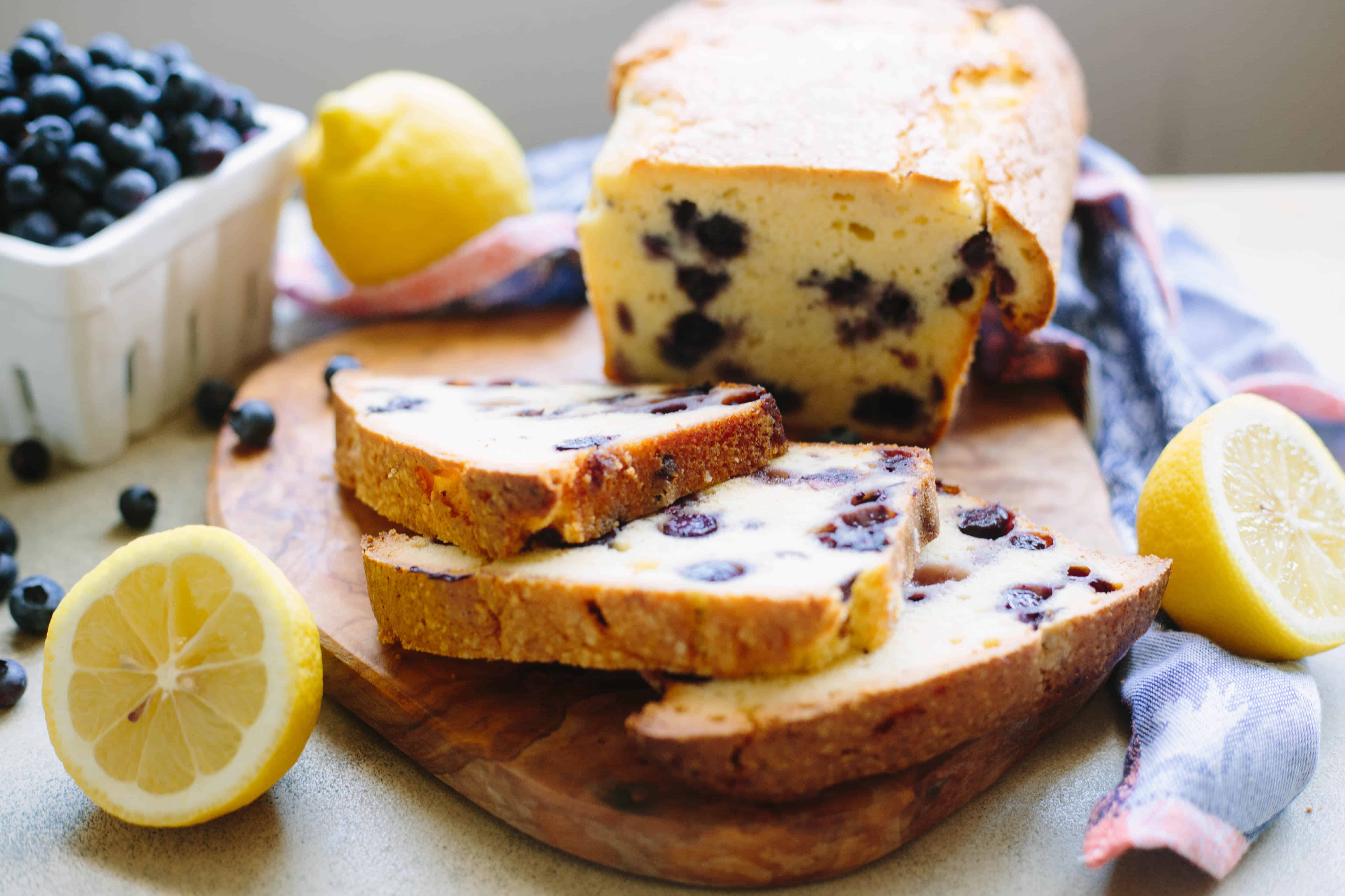 Three slices of lemon blueberry pound cake cut off a loaf on a wood cutting board.