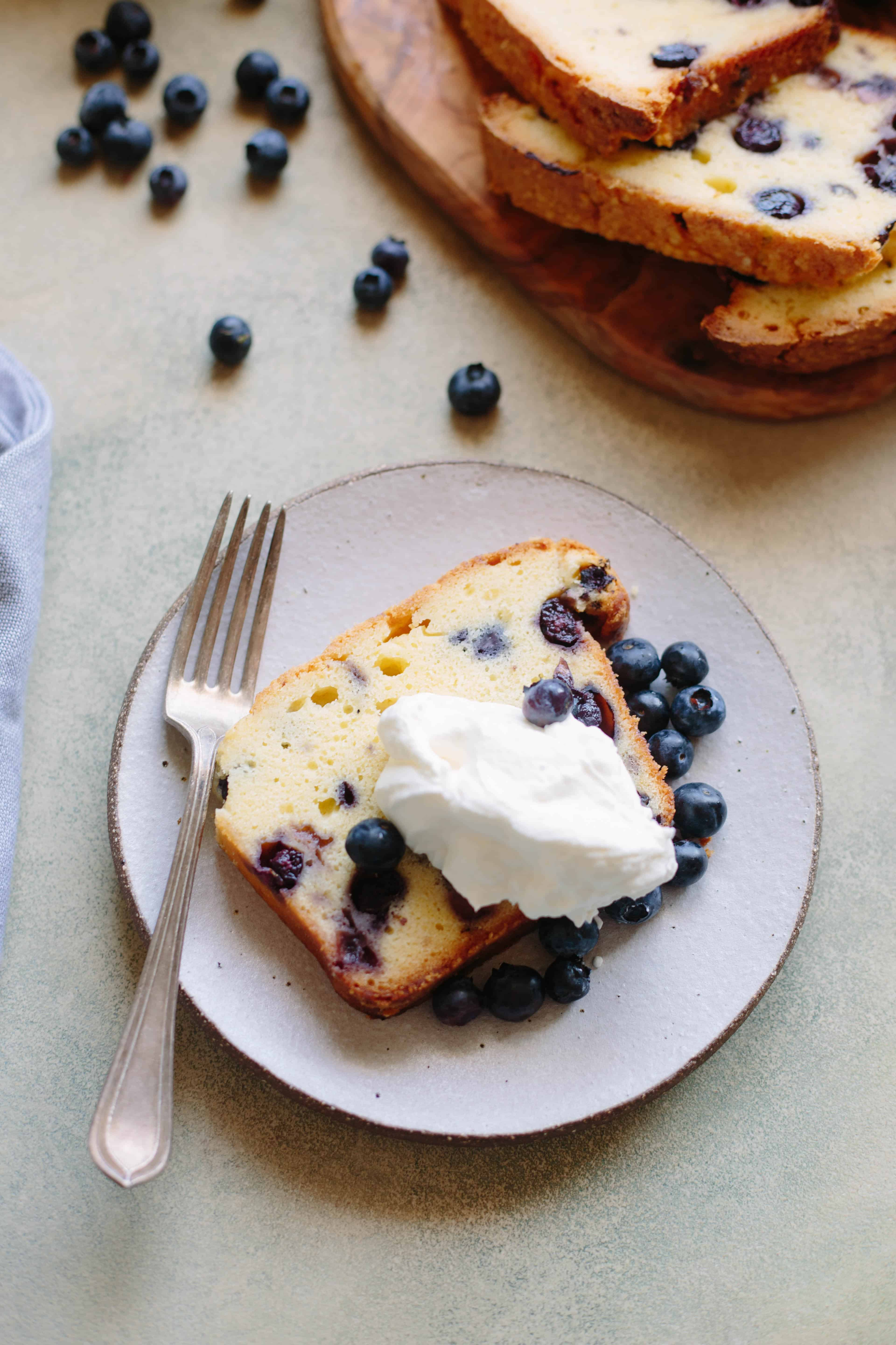 A slice of lemon blueberry pound cake topped with whipped cream on a dessert plate.
