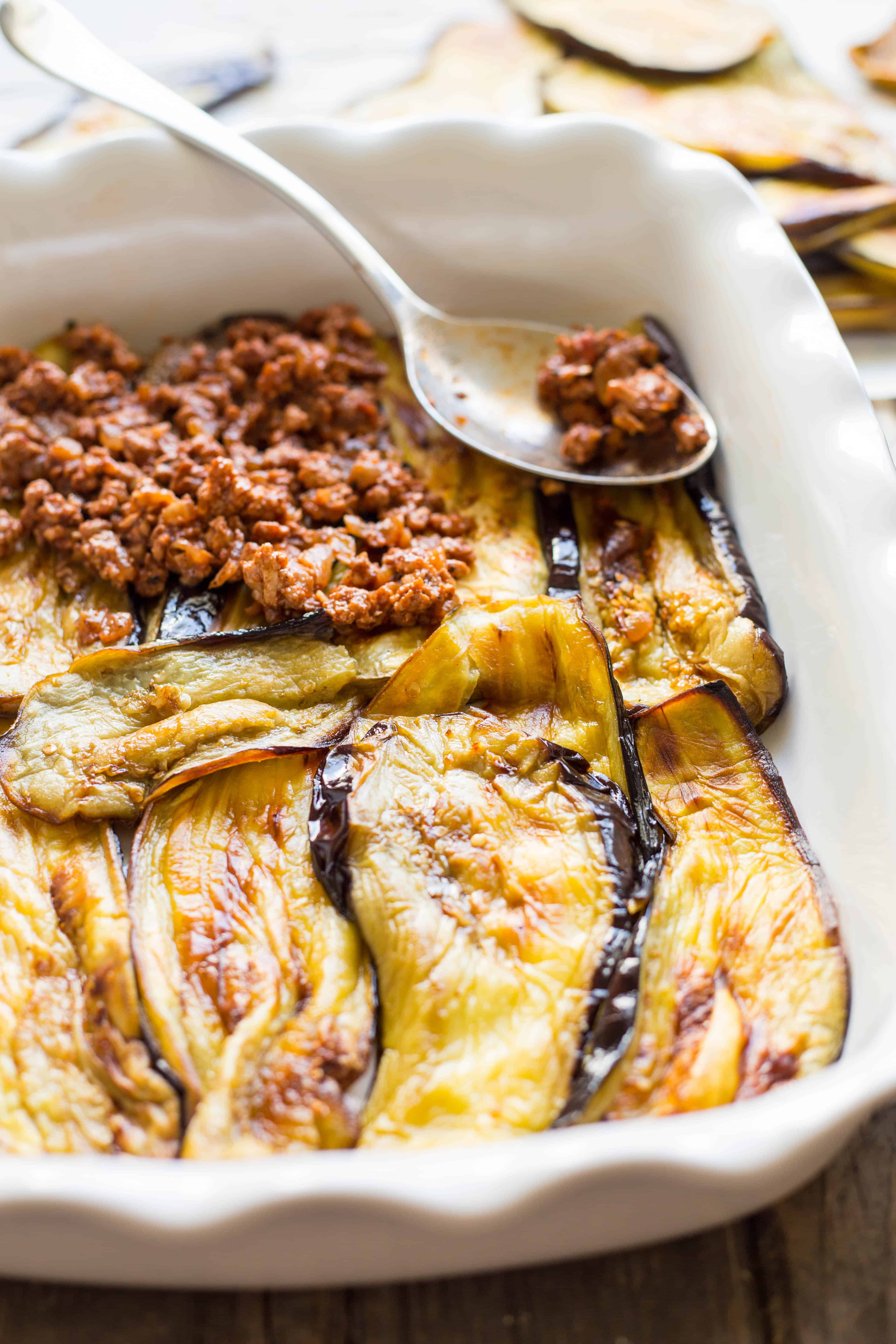 Close up of eggplant slices layered in a baking dish with ground turkey being spooned on top.