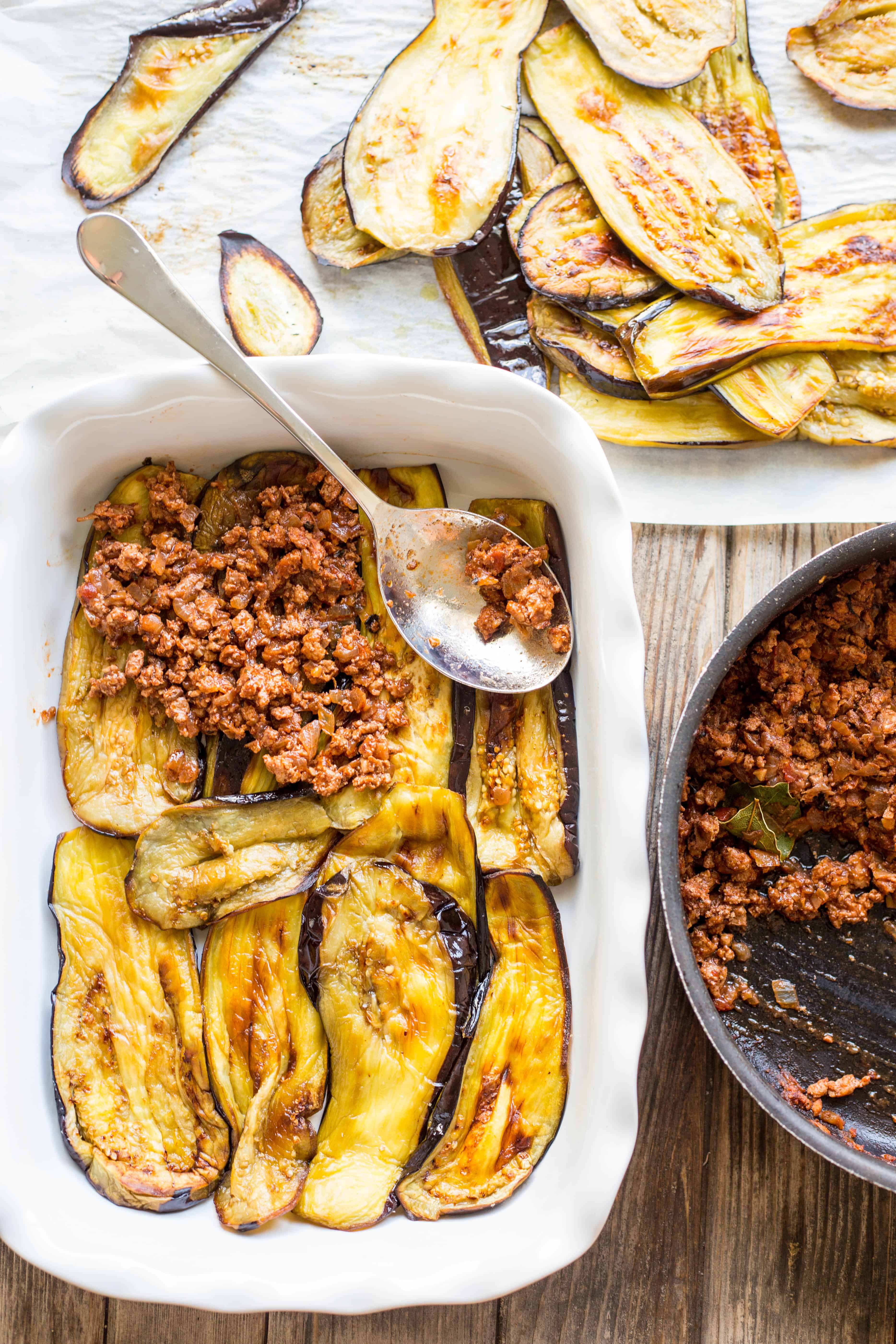 Assembling eggplant and ground turkey in a baking dish for moussaka.