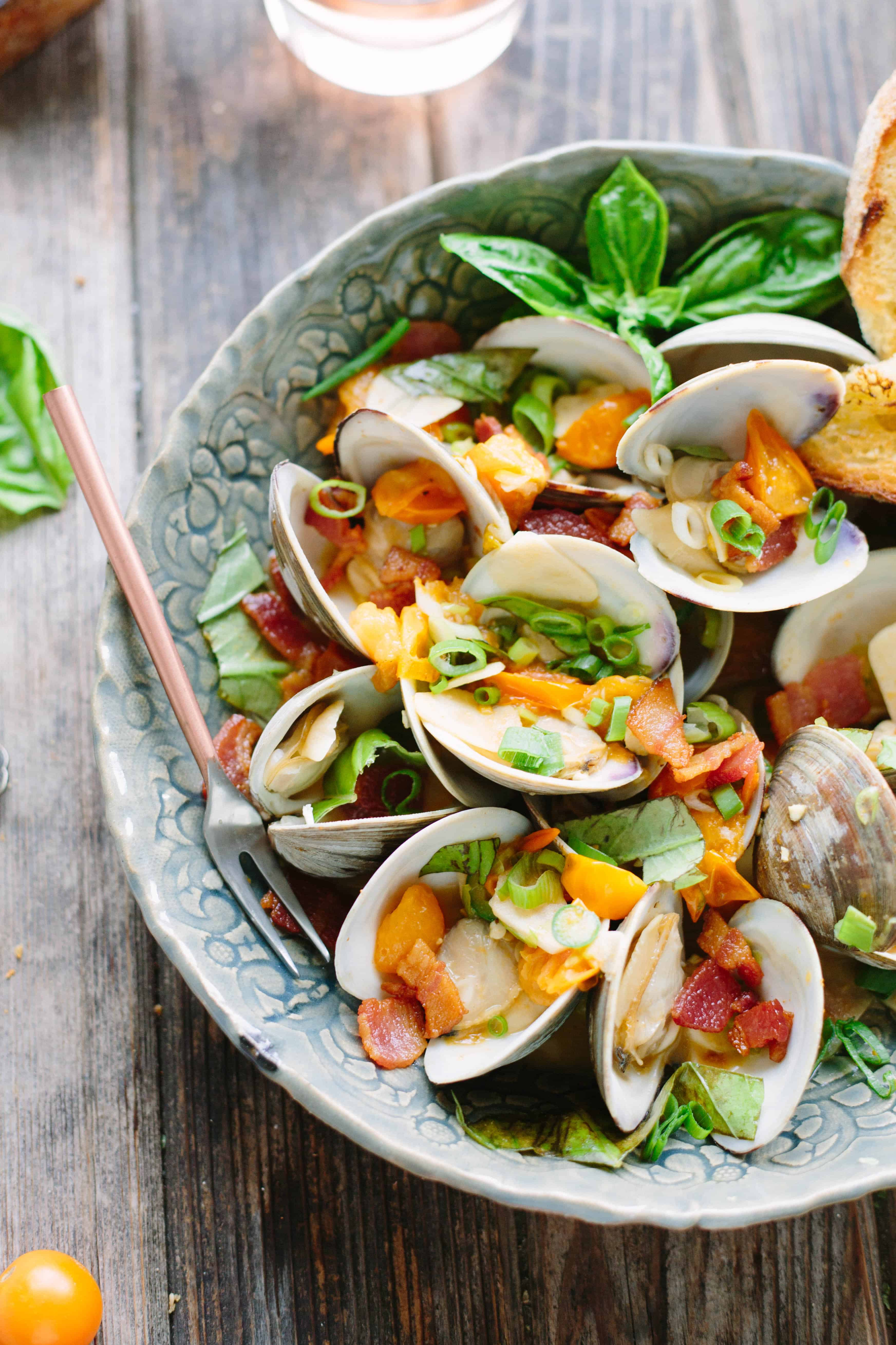 Large serving bowl of clams topped with bacon, tomatoes, and jalapenos.