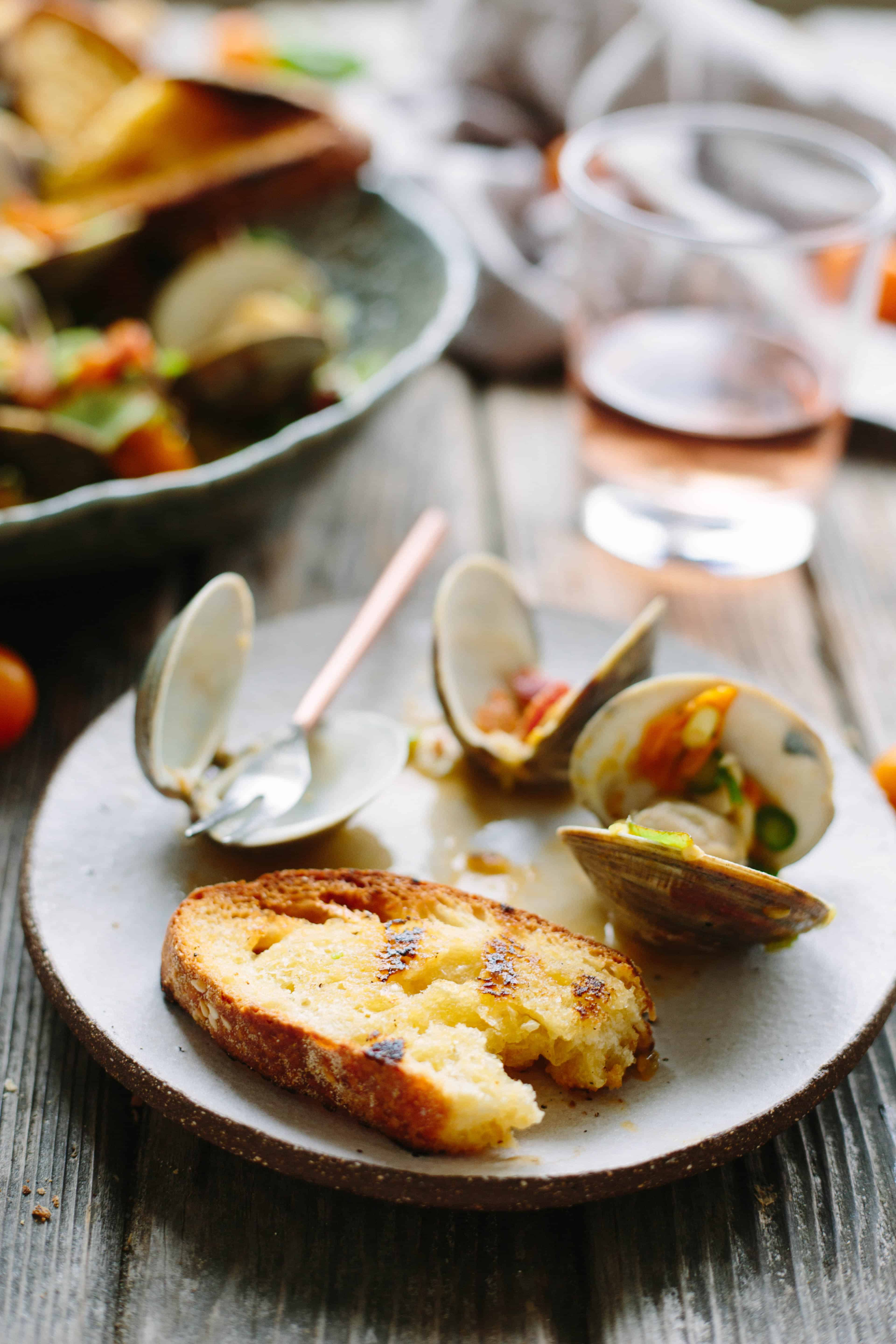 Toasted, buttered baguette and tomato topped clams on a white dinner plate.