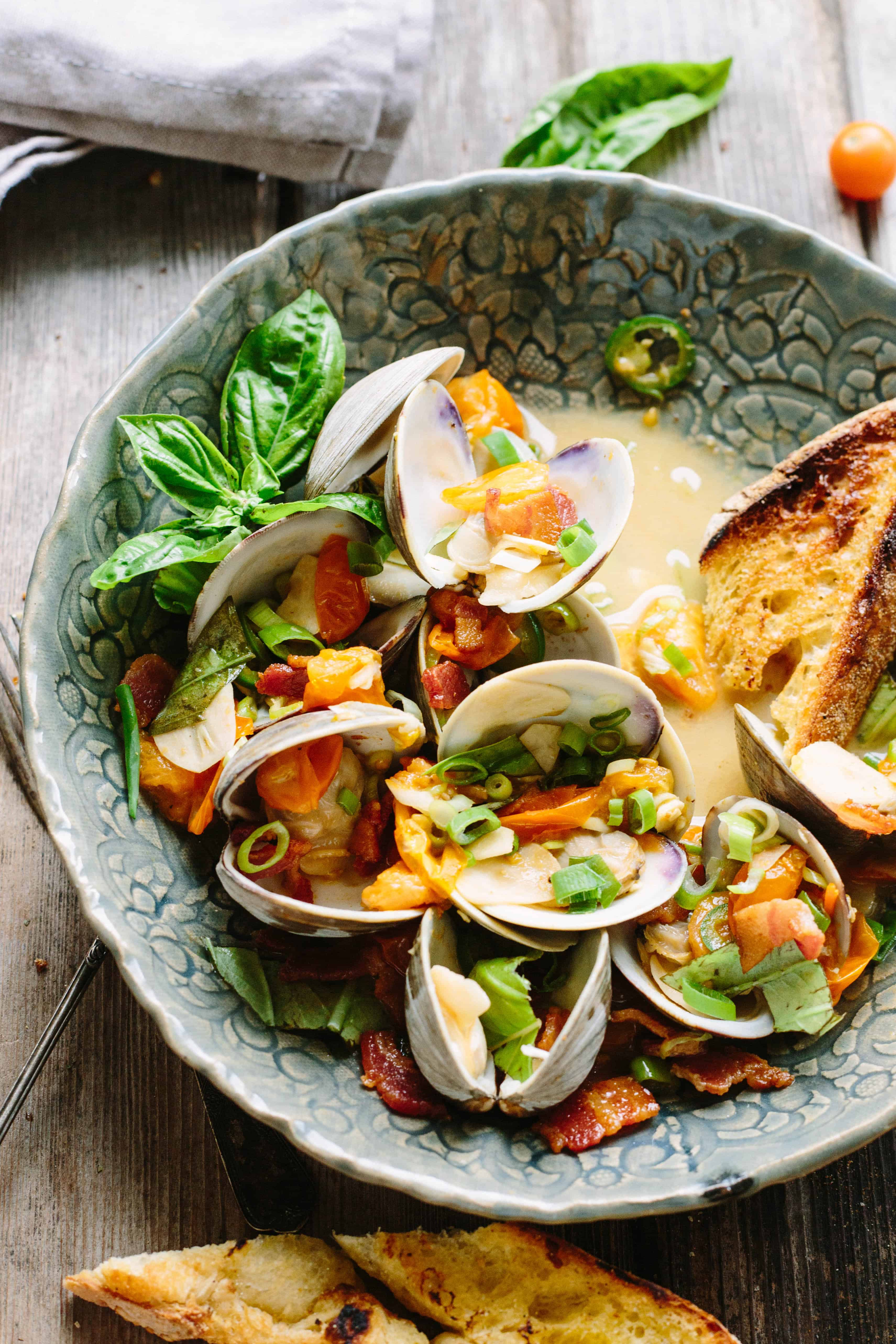 A serving bowl with tomato and jalapeno topped clams next to sliced and toasted baguette.