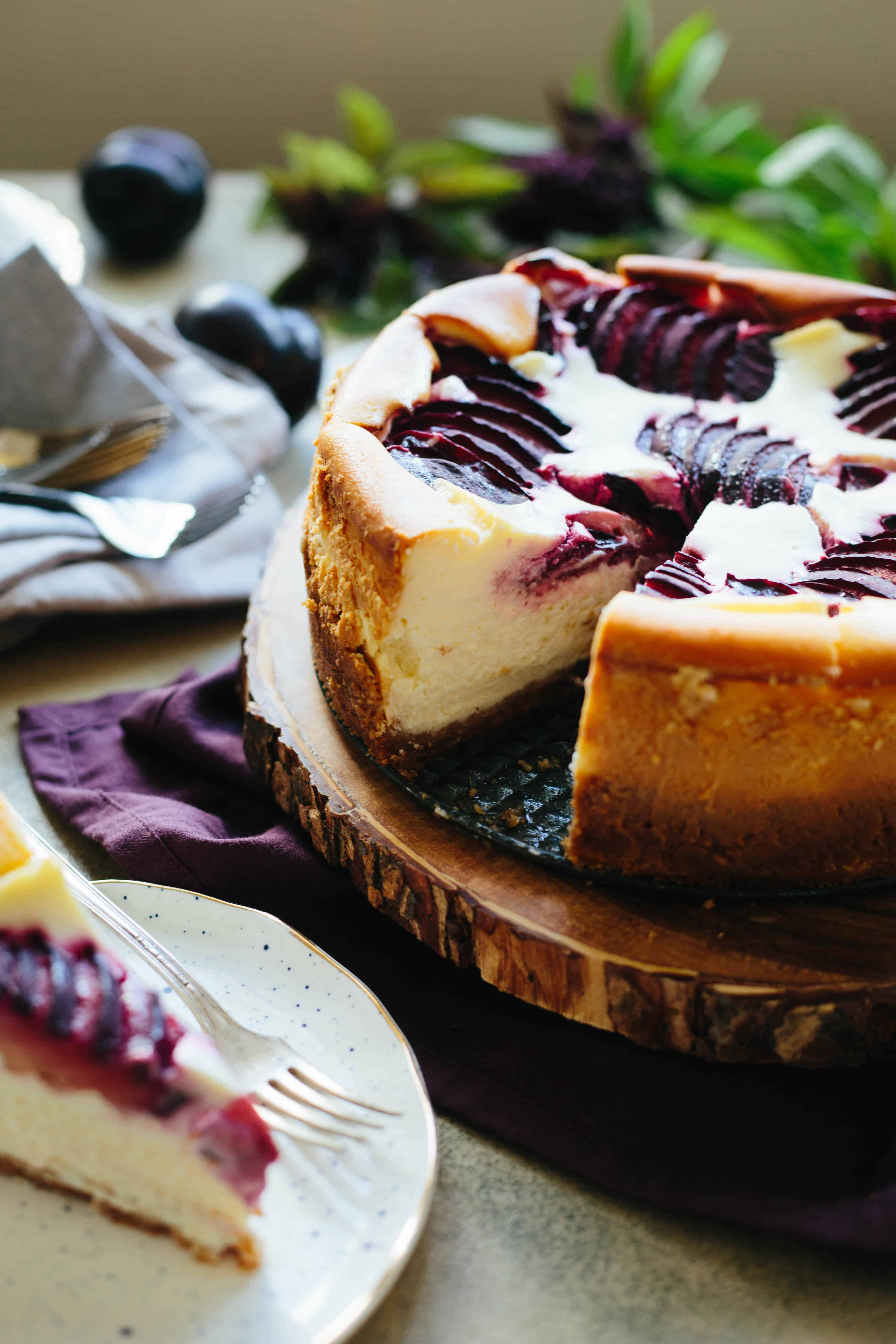 Plum ricotta cheesecake with a slice missing, sitting on a wood board.