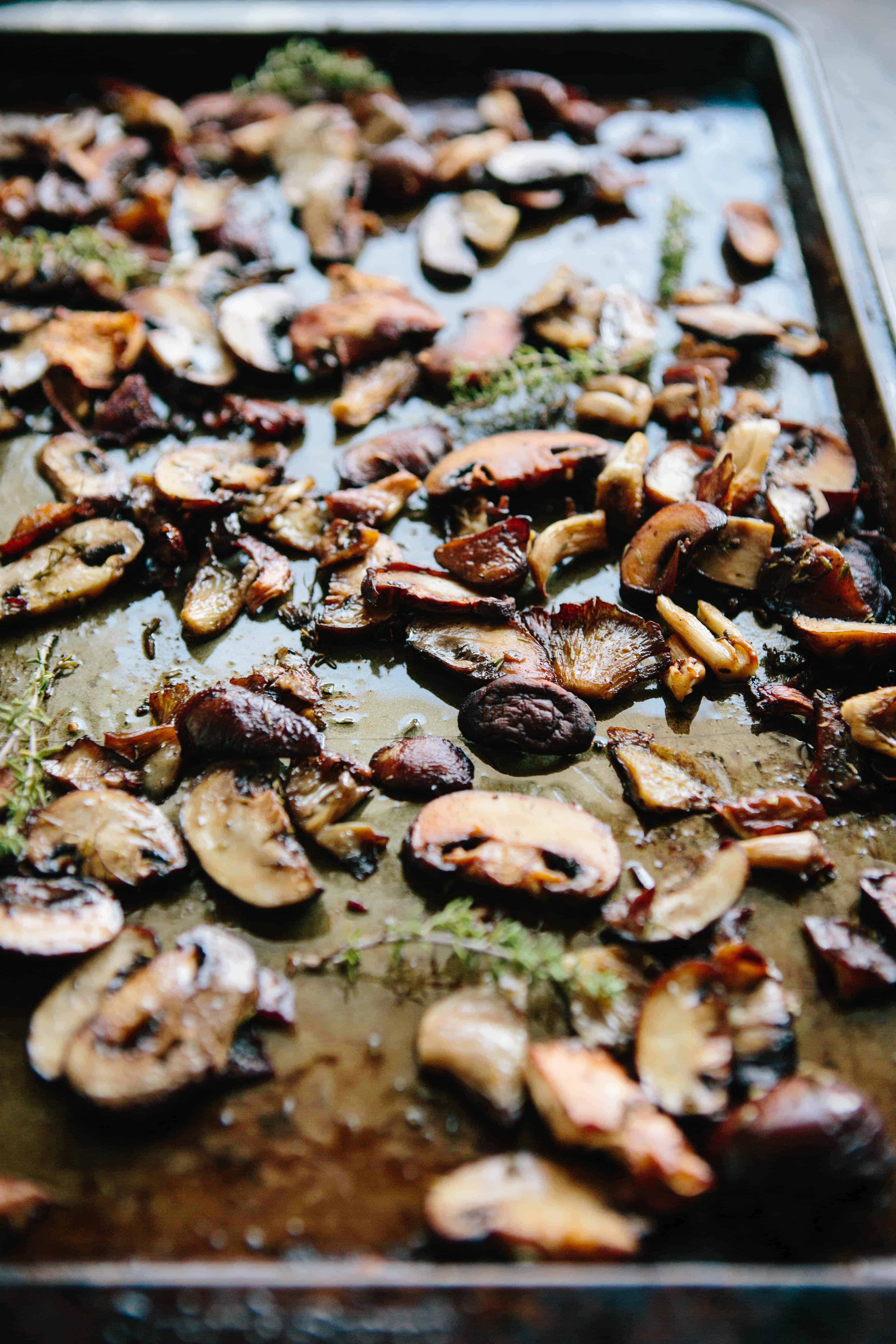 A baking sheet filled with sliced mushrooms and fresh herbs that have been roasted.