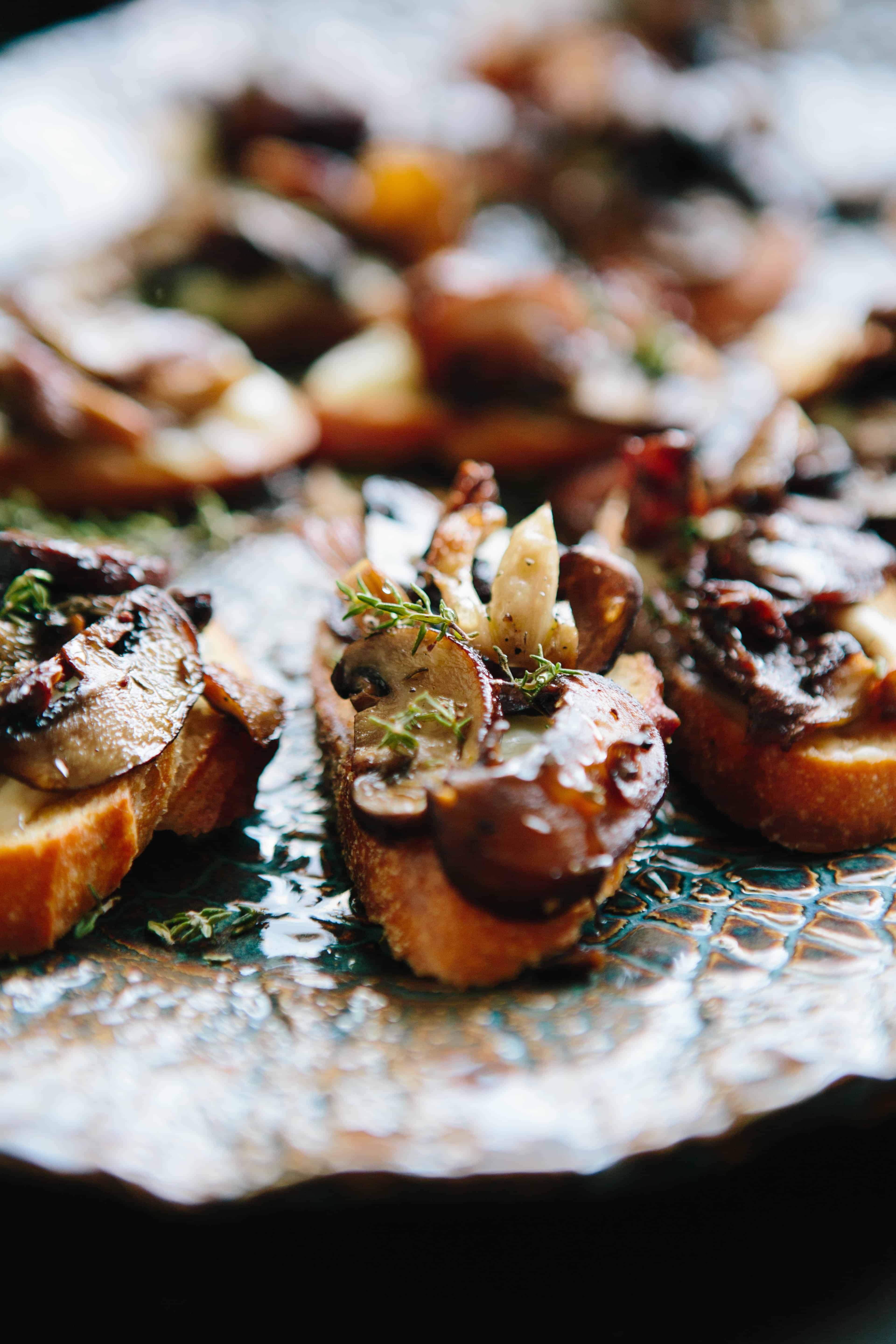 Angled shot of roasted mushroom and cheese crostini on a serving tray.