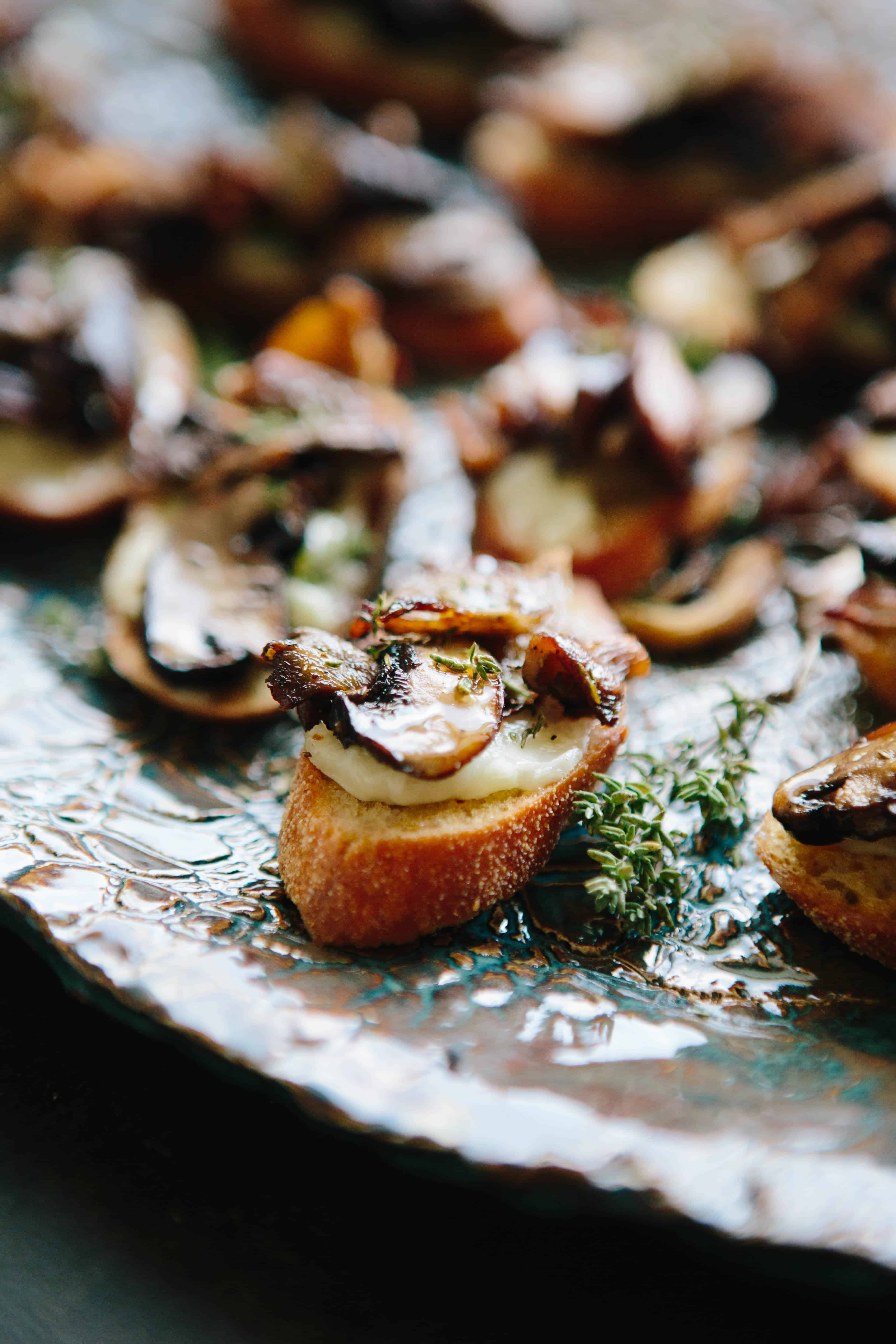 Close up of mushroom and cheese on crostini on a serving platter.