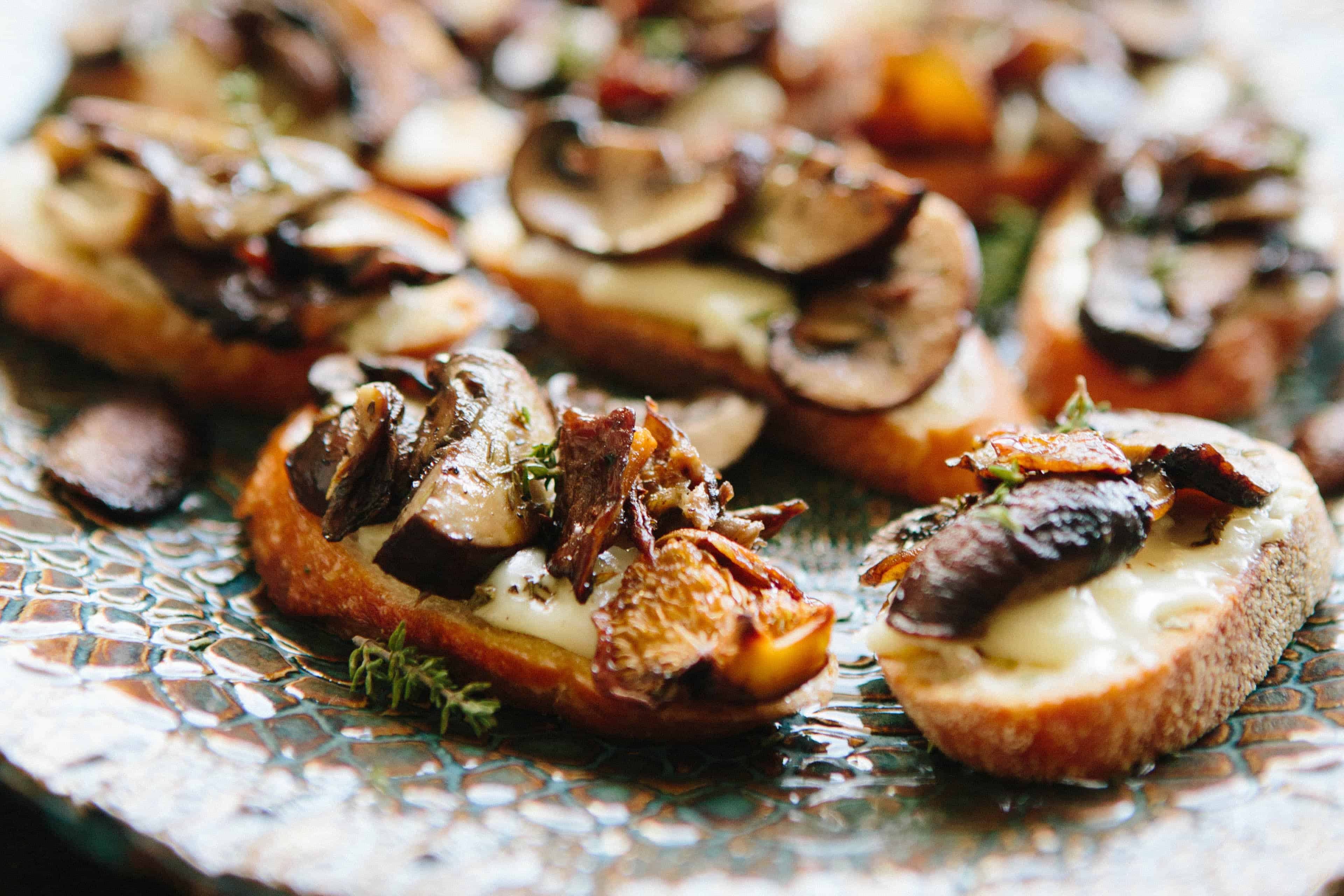 A close up of crostini on a serving platter topped with cheese and roasted mushrooms.