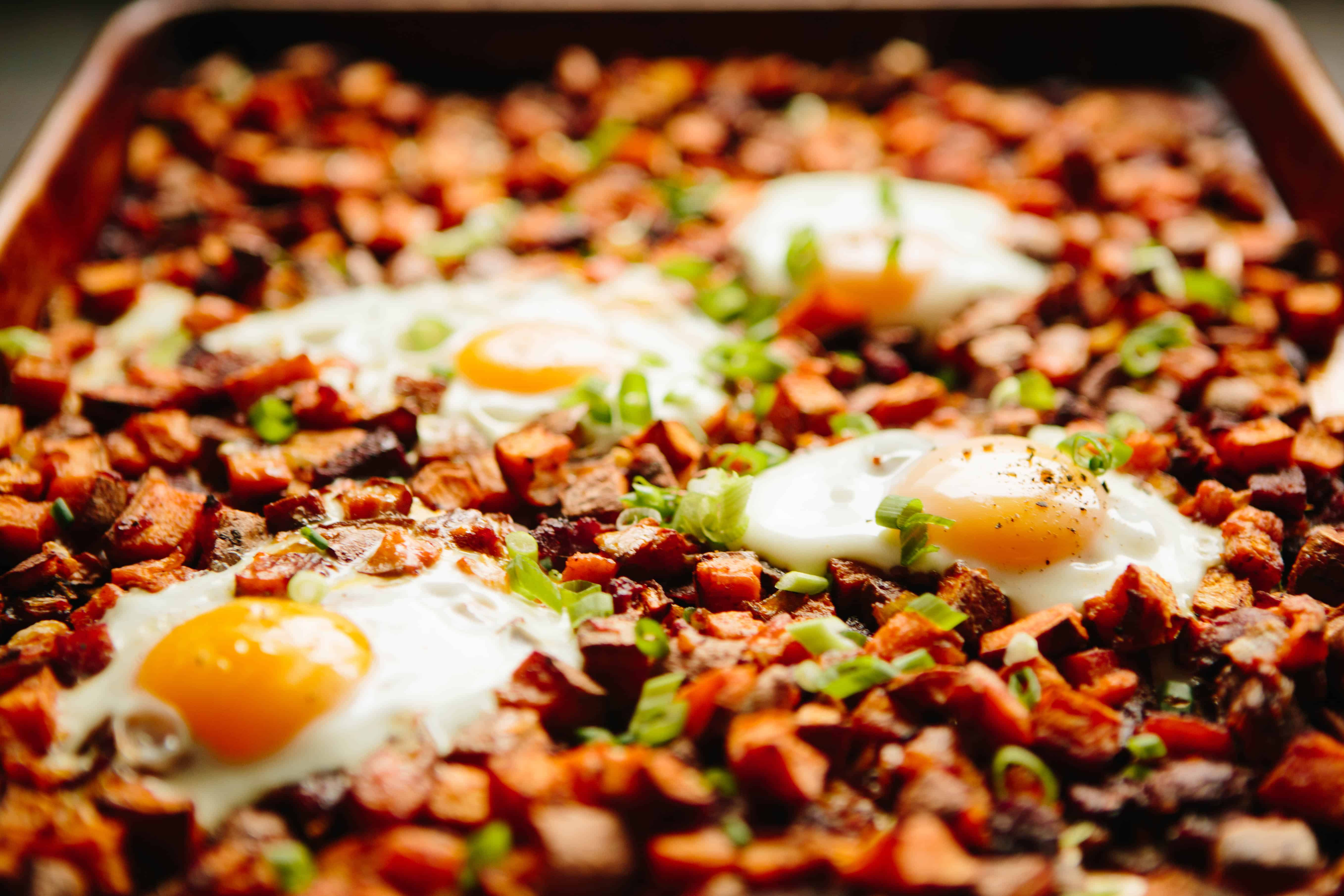 Angled shot of a pan of chorizo potato hash with runny eggs baked on top.