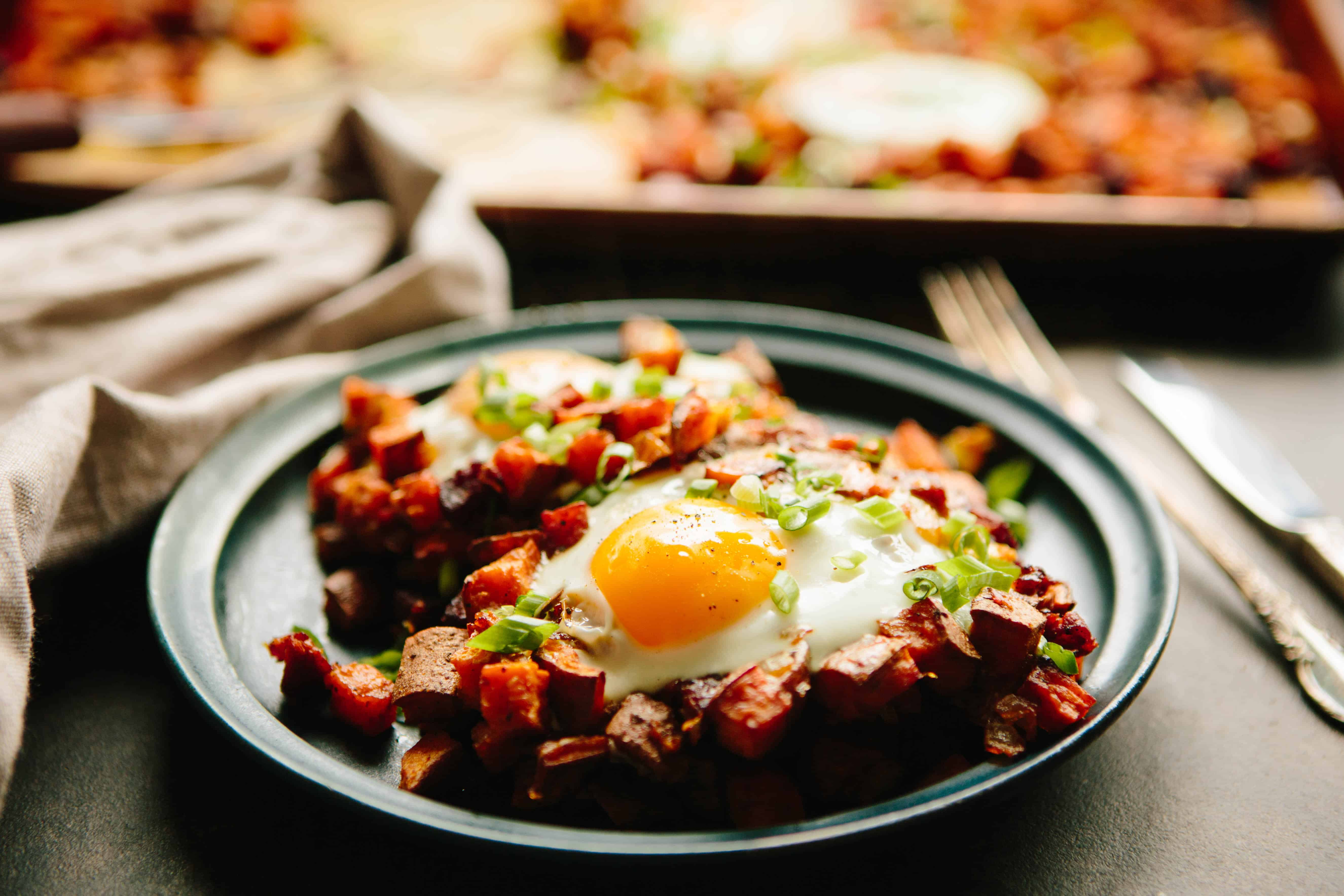 Dinner plate filled with sweet potato chorizo hash and runny eggs.