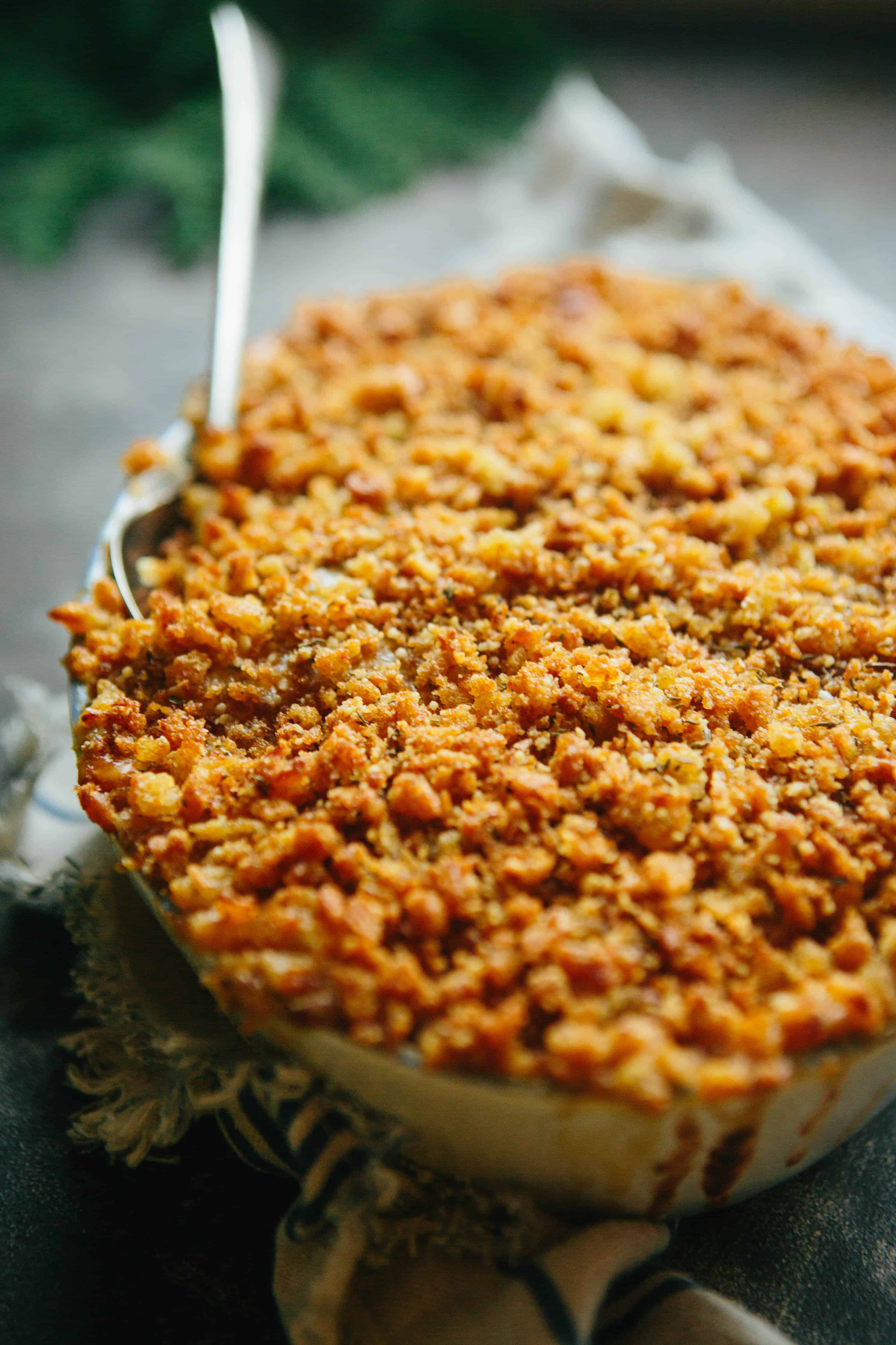 Close up of crunchy topped kale gratin in a baking dish, with a serving spoon.