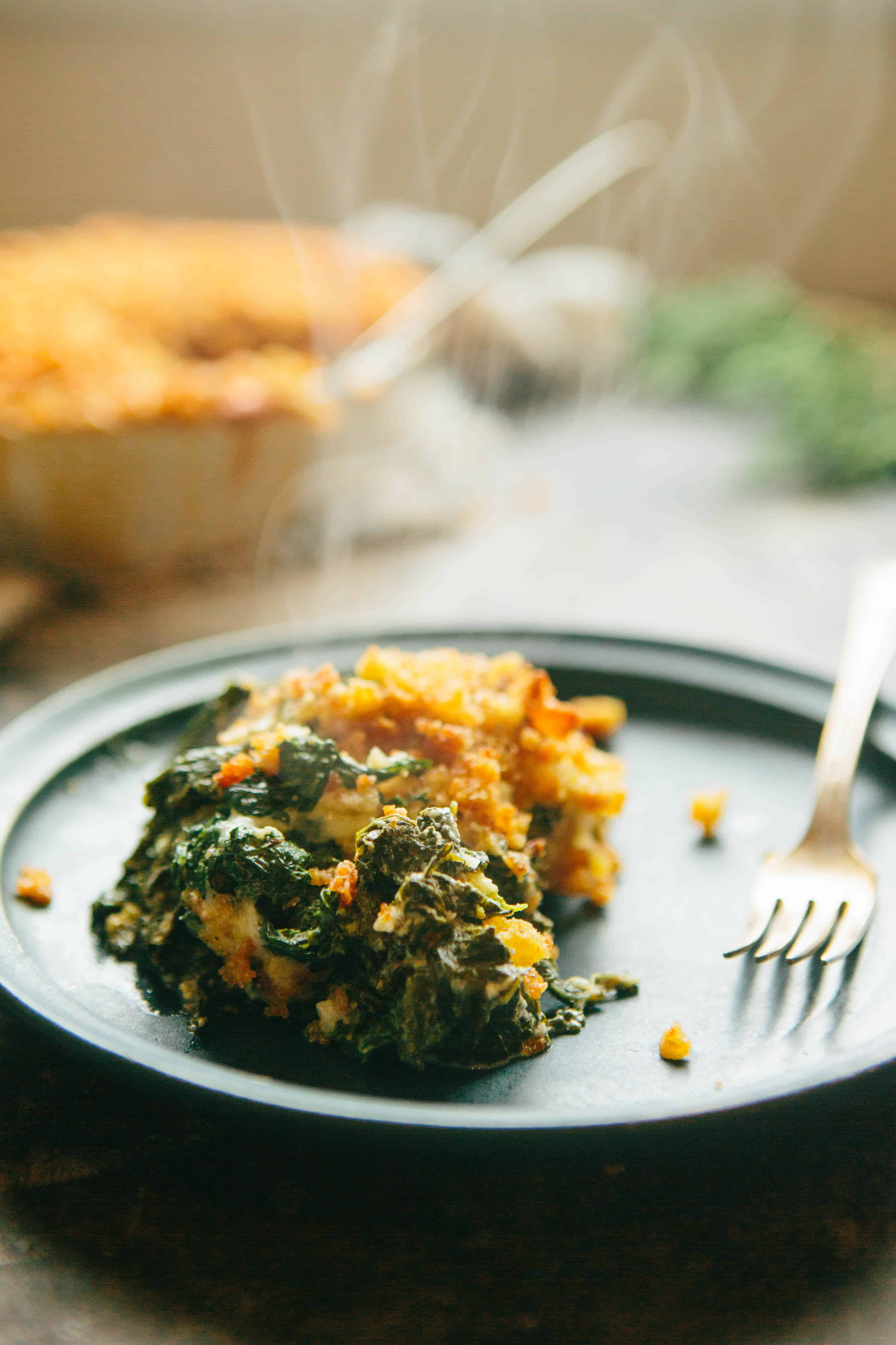 Cheese kale gratin on a small blue plate with a fork.