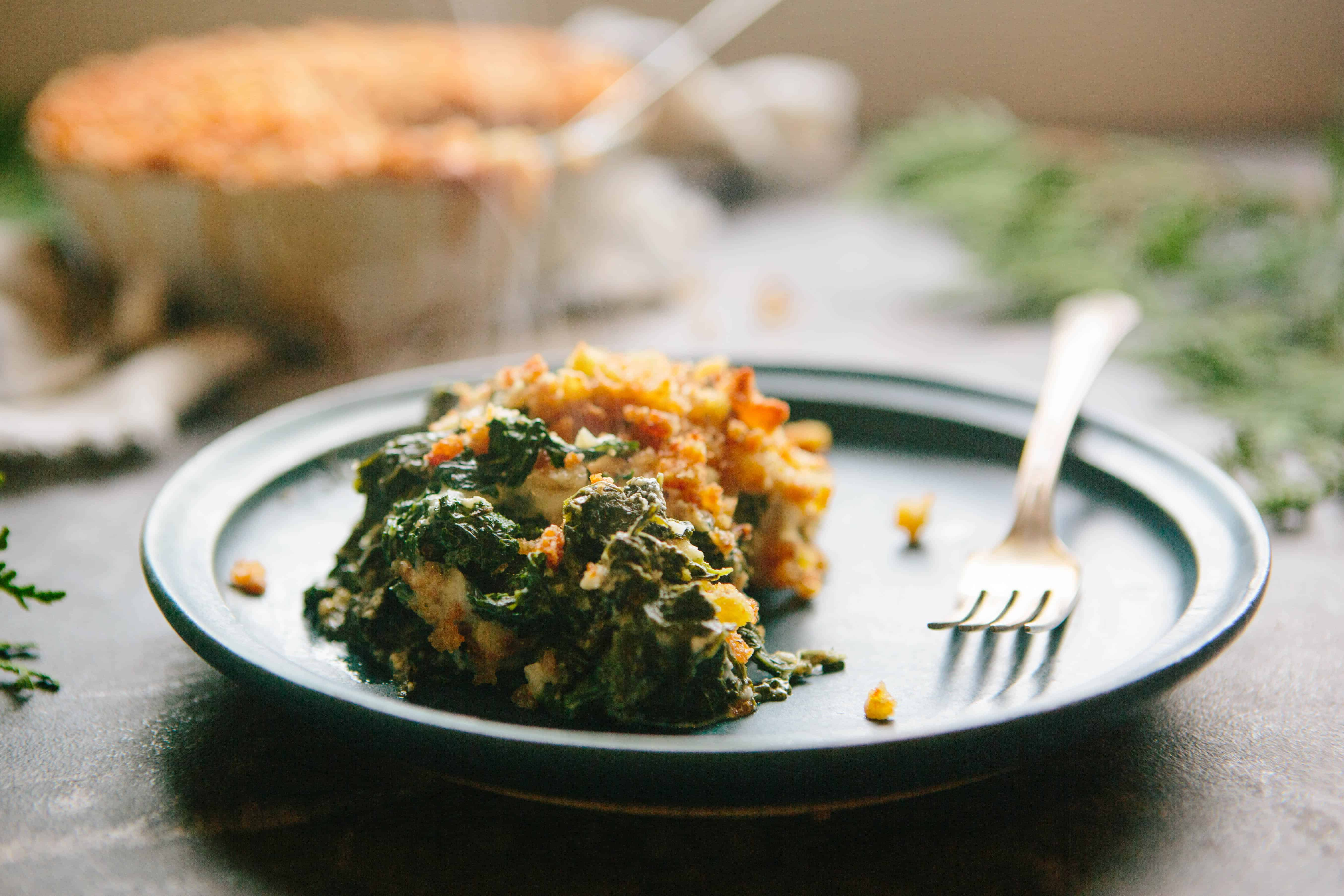 Steaming creamy kale gratin on a small plate with a fork.