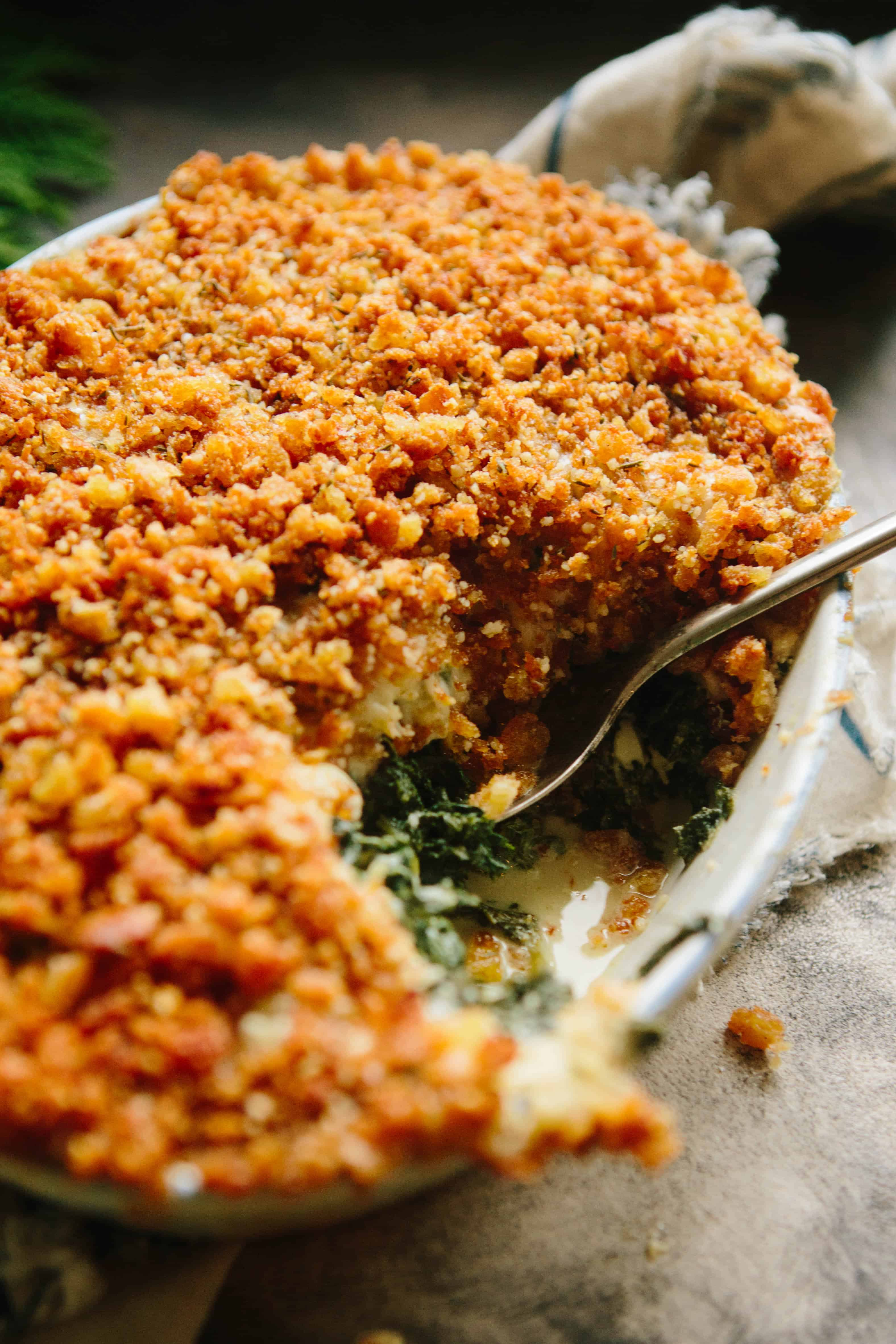 A casserole dish of kale gratin with a serving spoon, missing one serving.