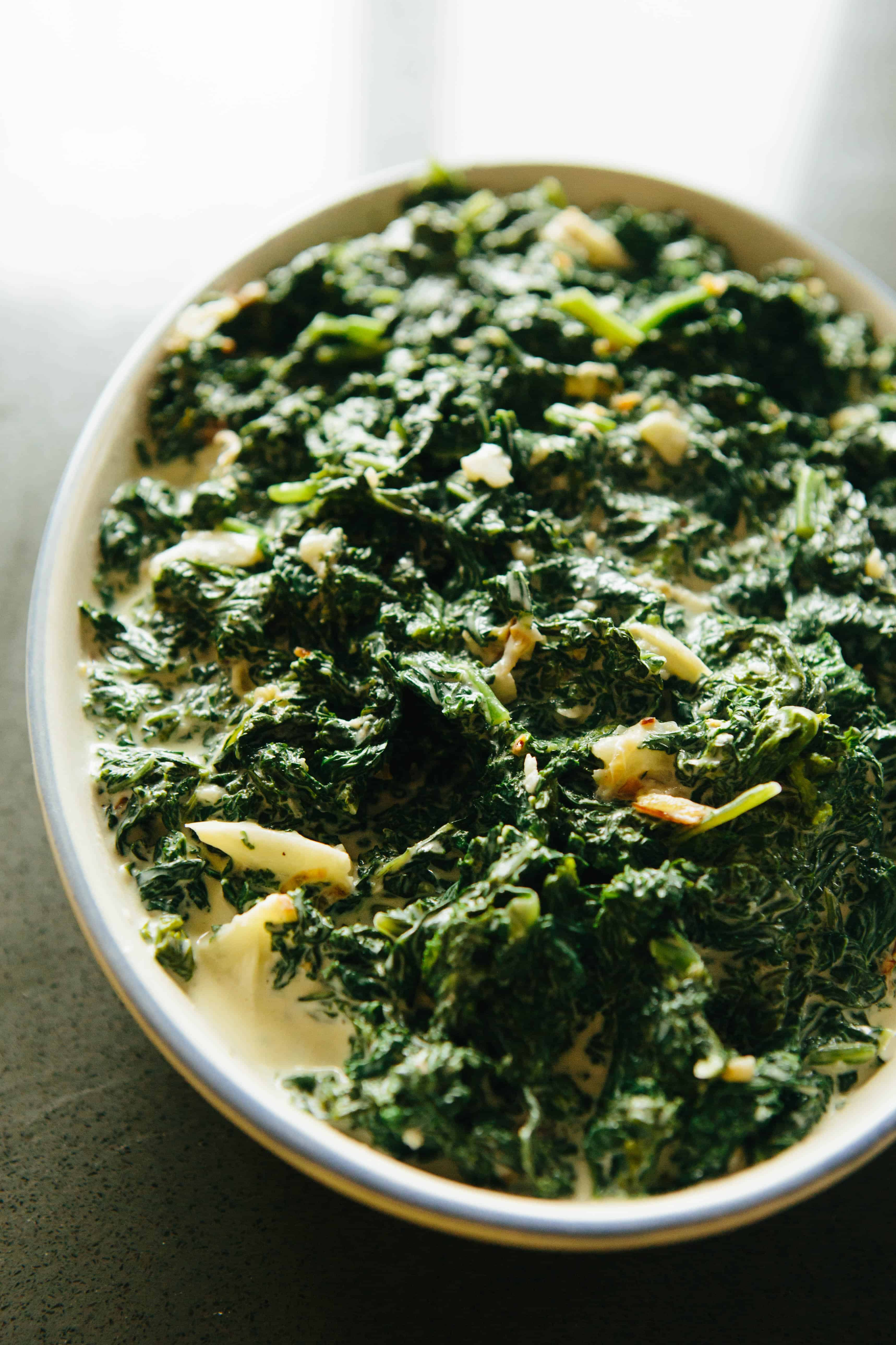 Cheesy kale gratin in a baking dish, before any topping has been added.
