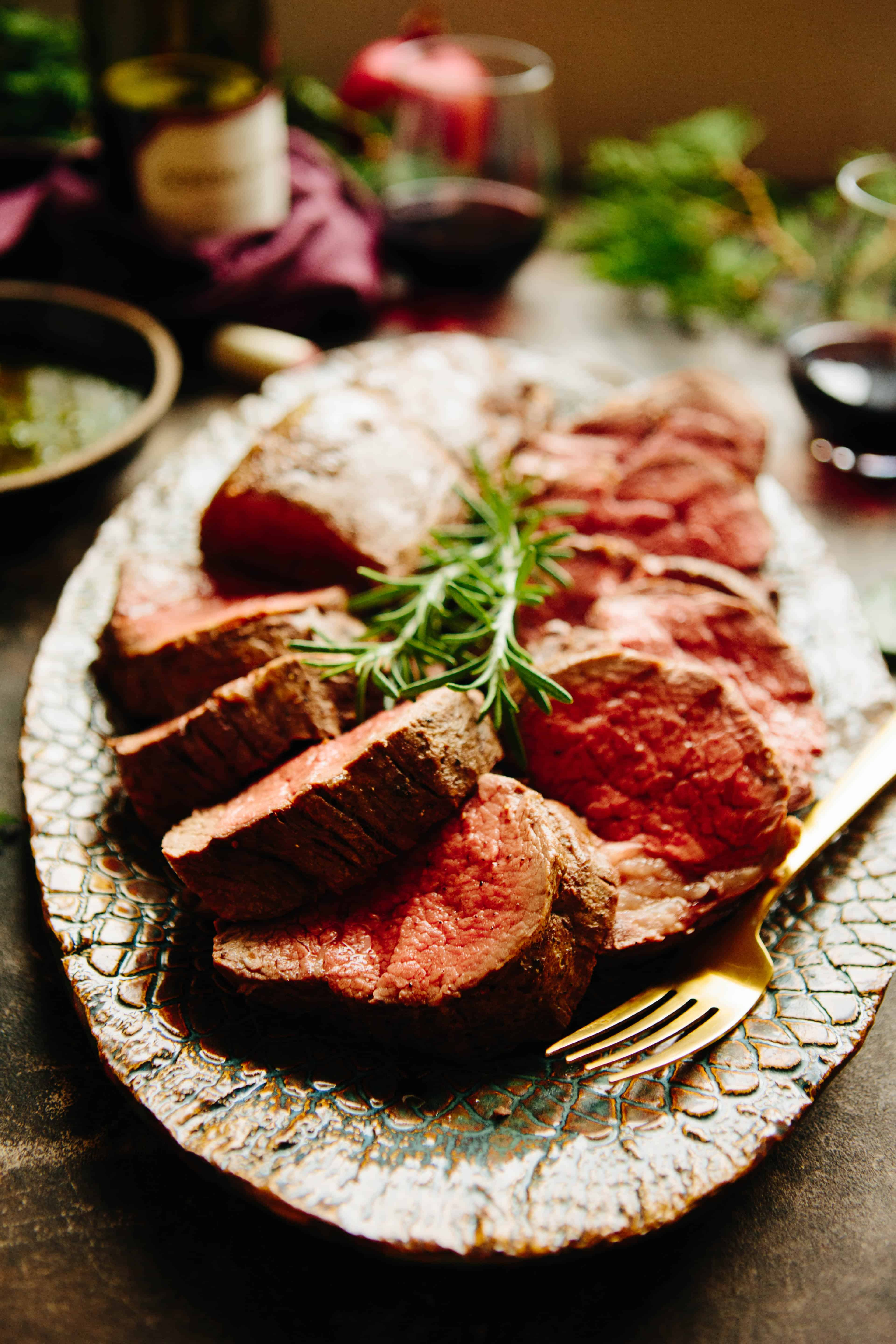 Sliced rare beef tenderloin on serving platter with rosemary garnish and gold fork