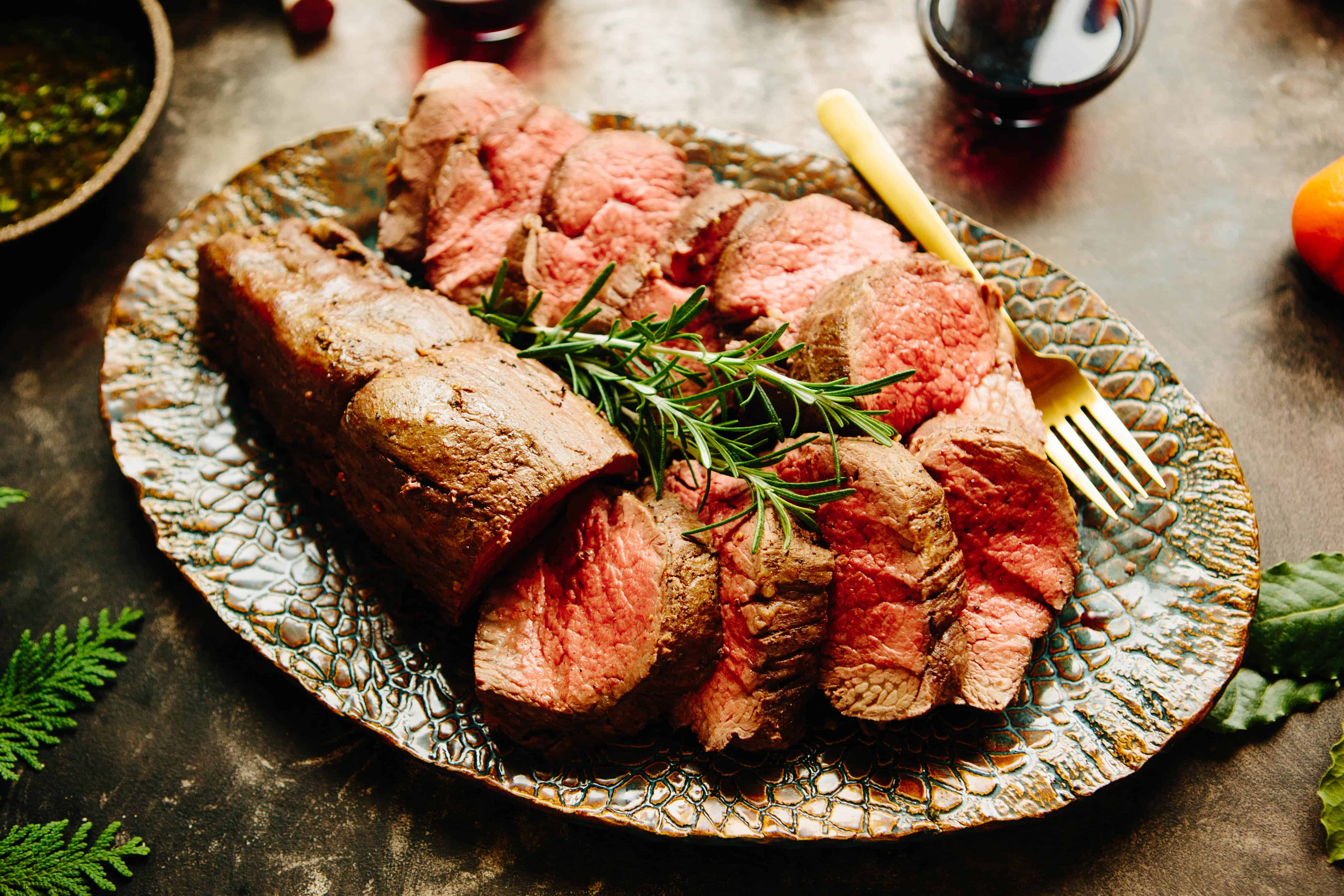 Platter of sliced rare Whole Roasted Beef Tenderloin with rosemary garnish and gold fork