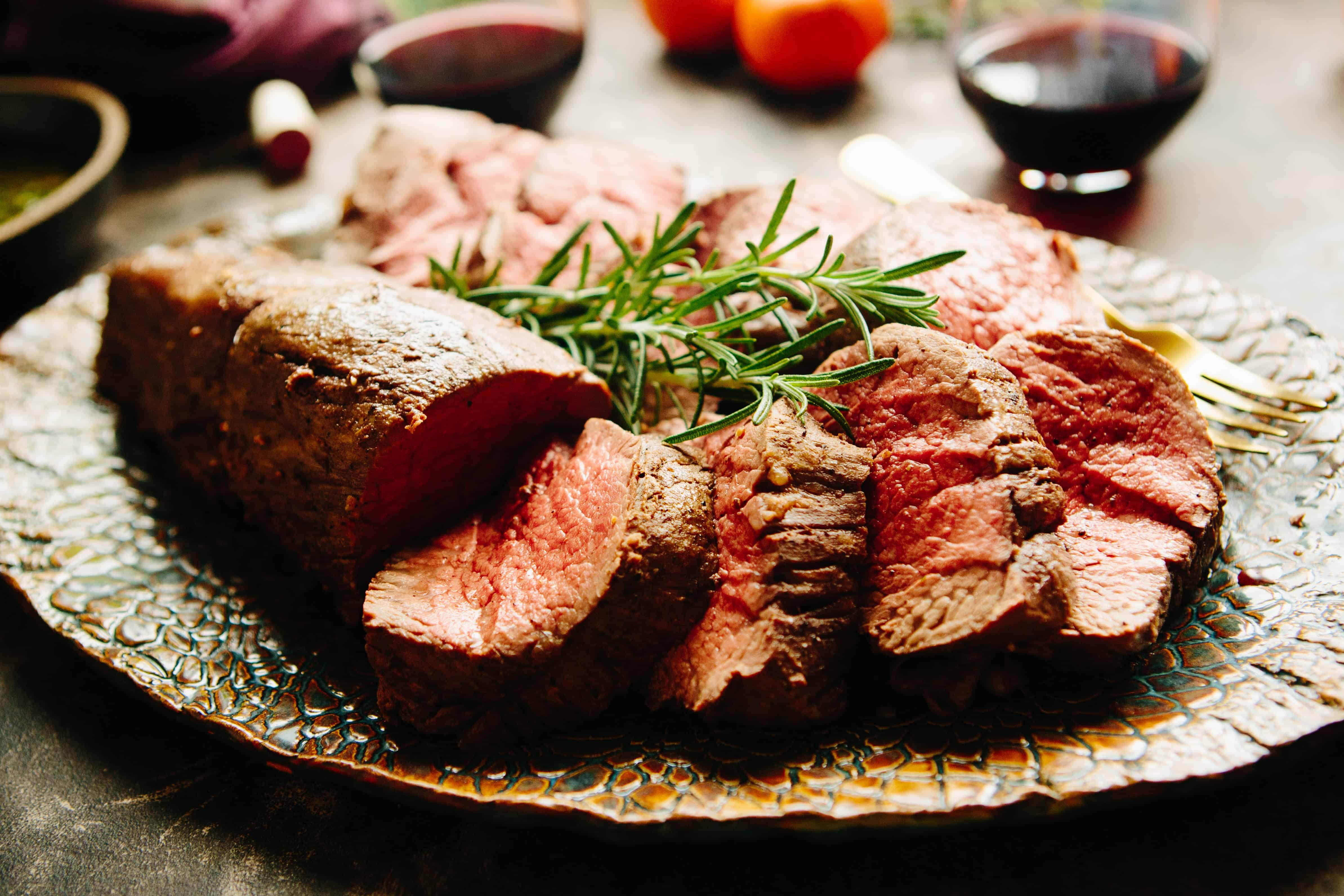 Whole Roasted Beef Tenderloin sliced on a platter, rare, with rosemary garnish. glass of red wine in background