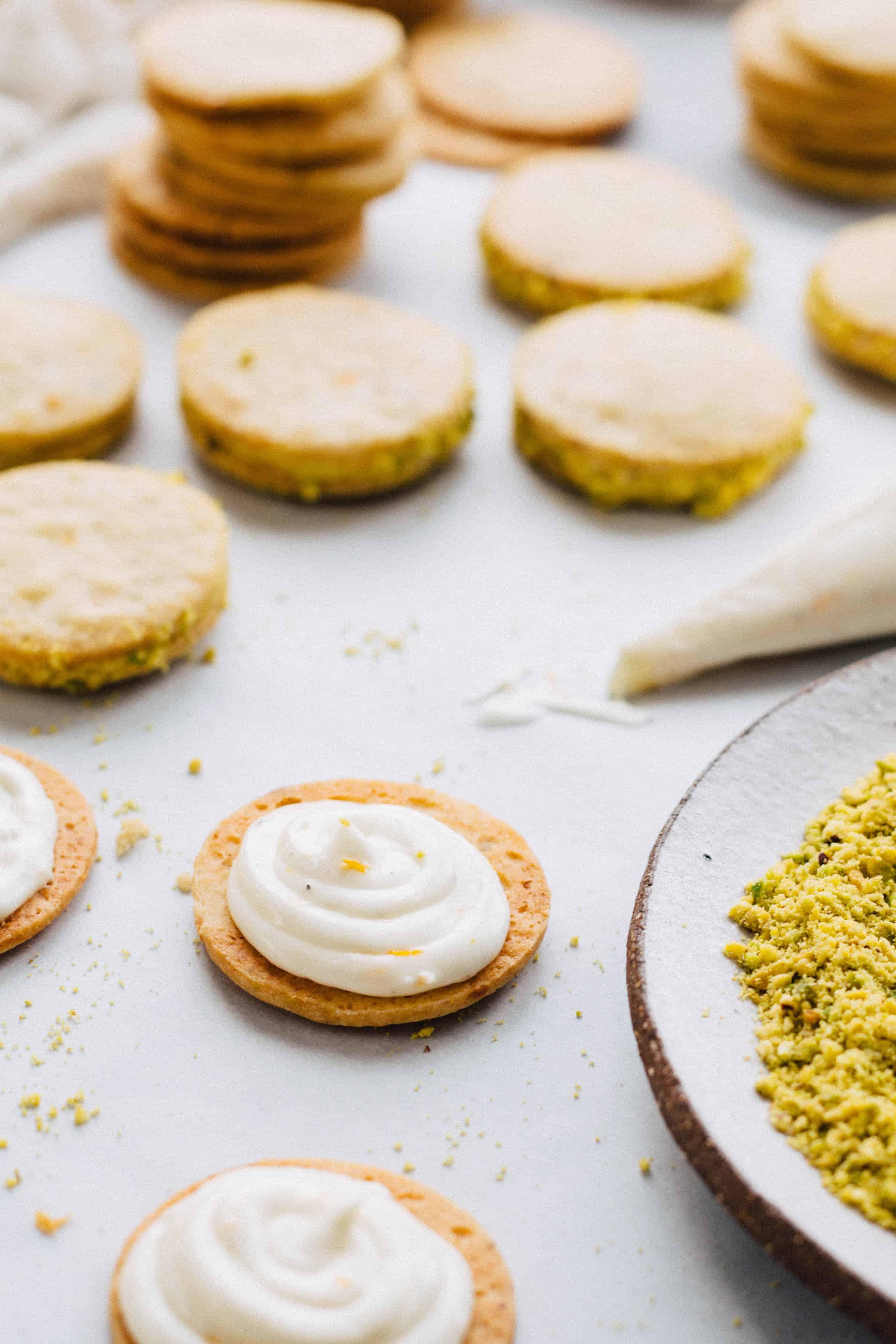 A pastry bag adding filling to a lemon pistachio cookie half.