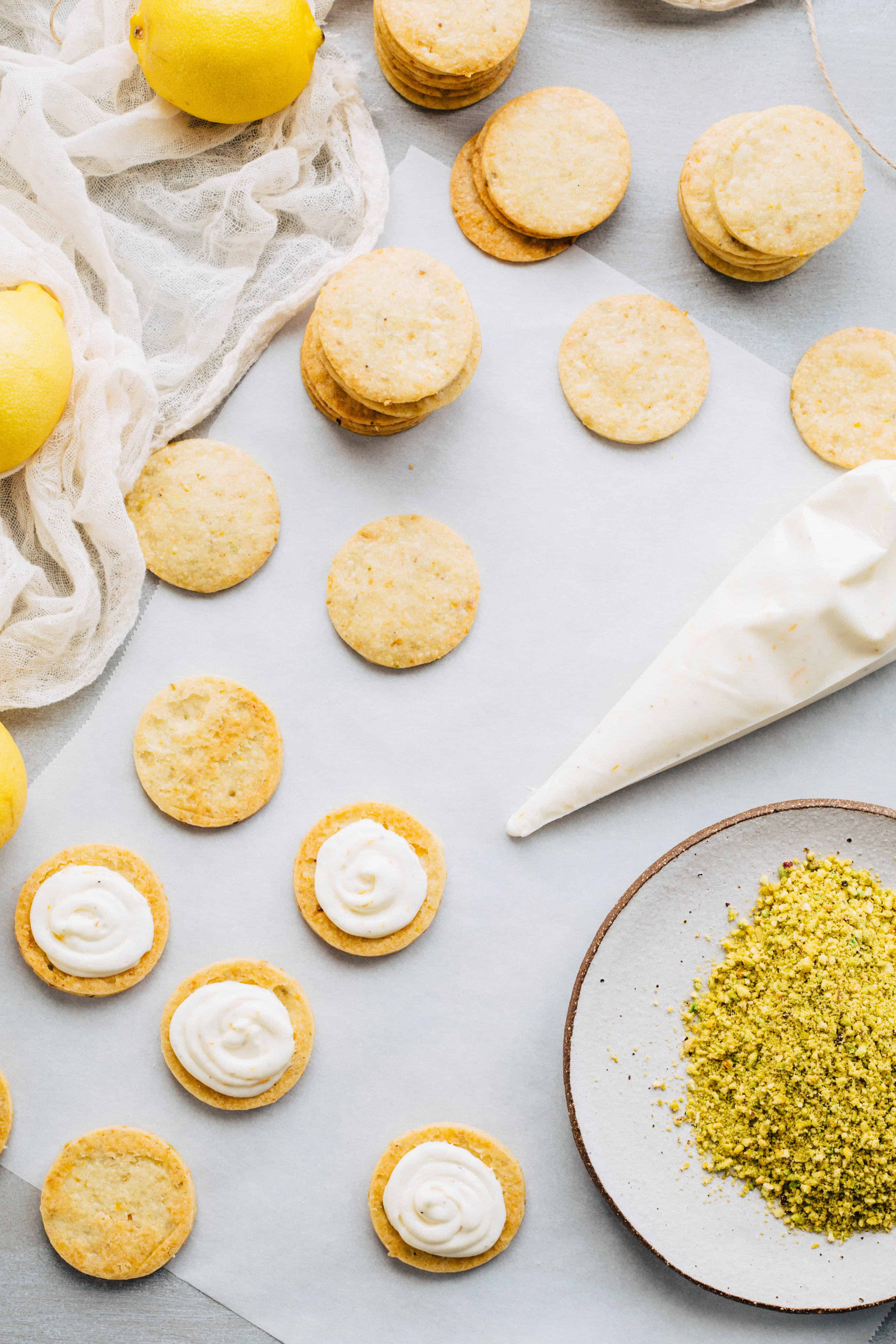 A pastry bag of filling and lemon pistachio cookies on a table, half of them with filling.