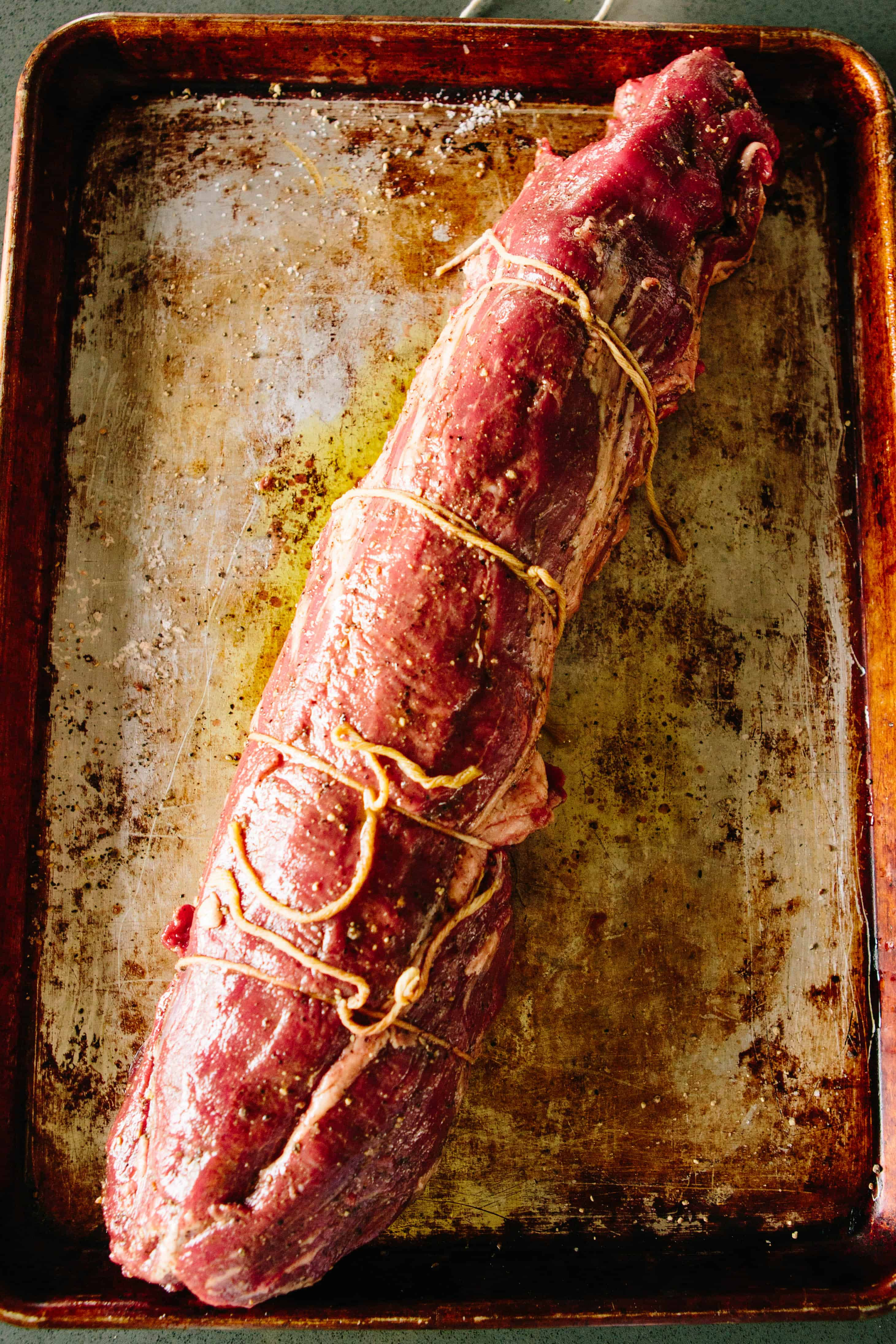 whole raw beef tenderloin on a sheet pan, tied with twine and seasoned with salt, pepper and olive oil