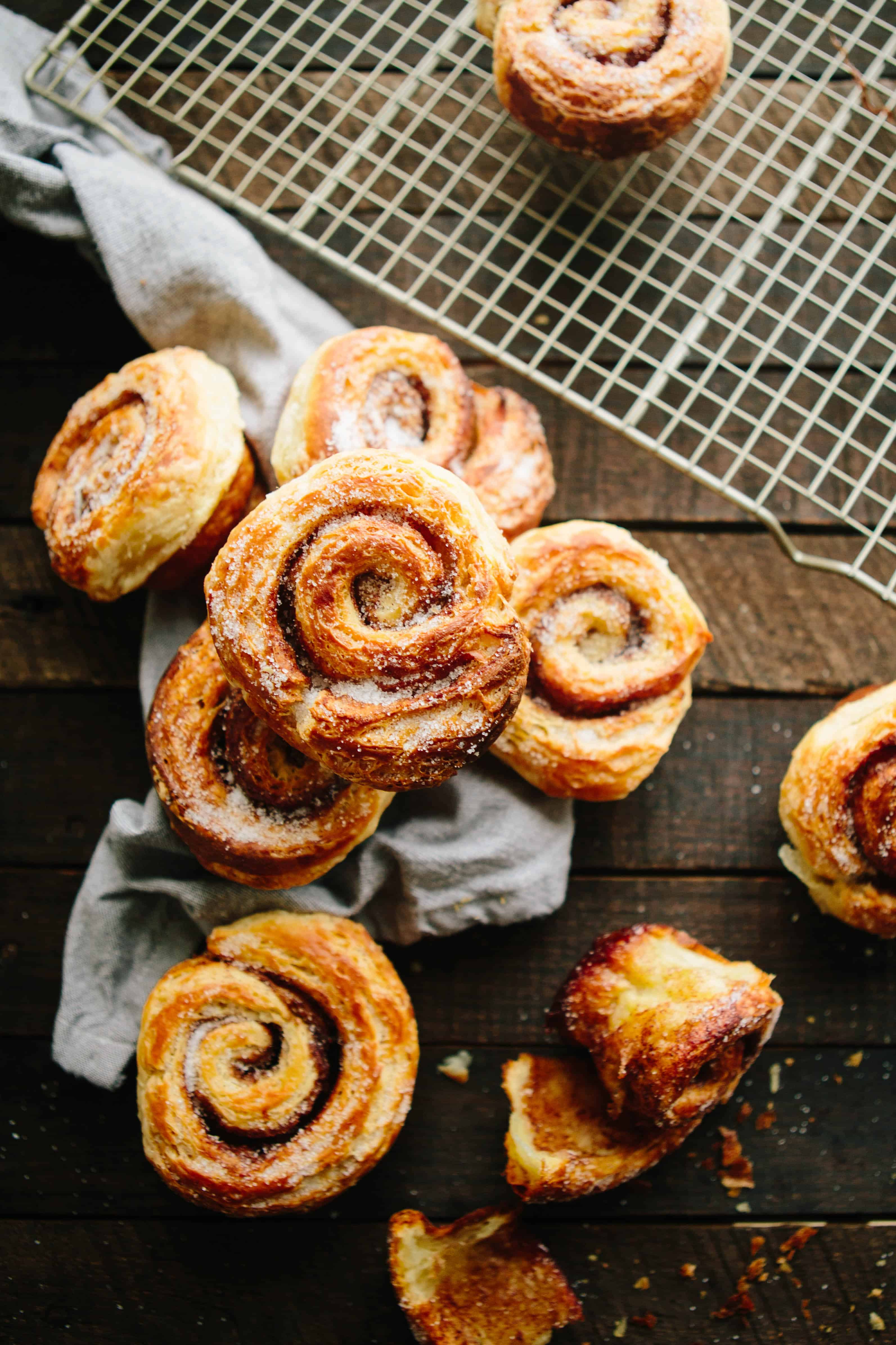 A pile of croissant morning buns on a wood board.