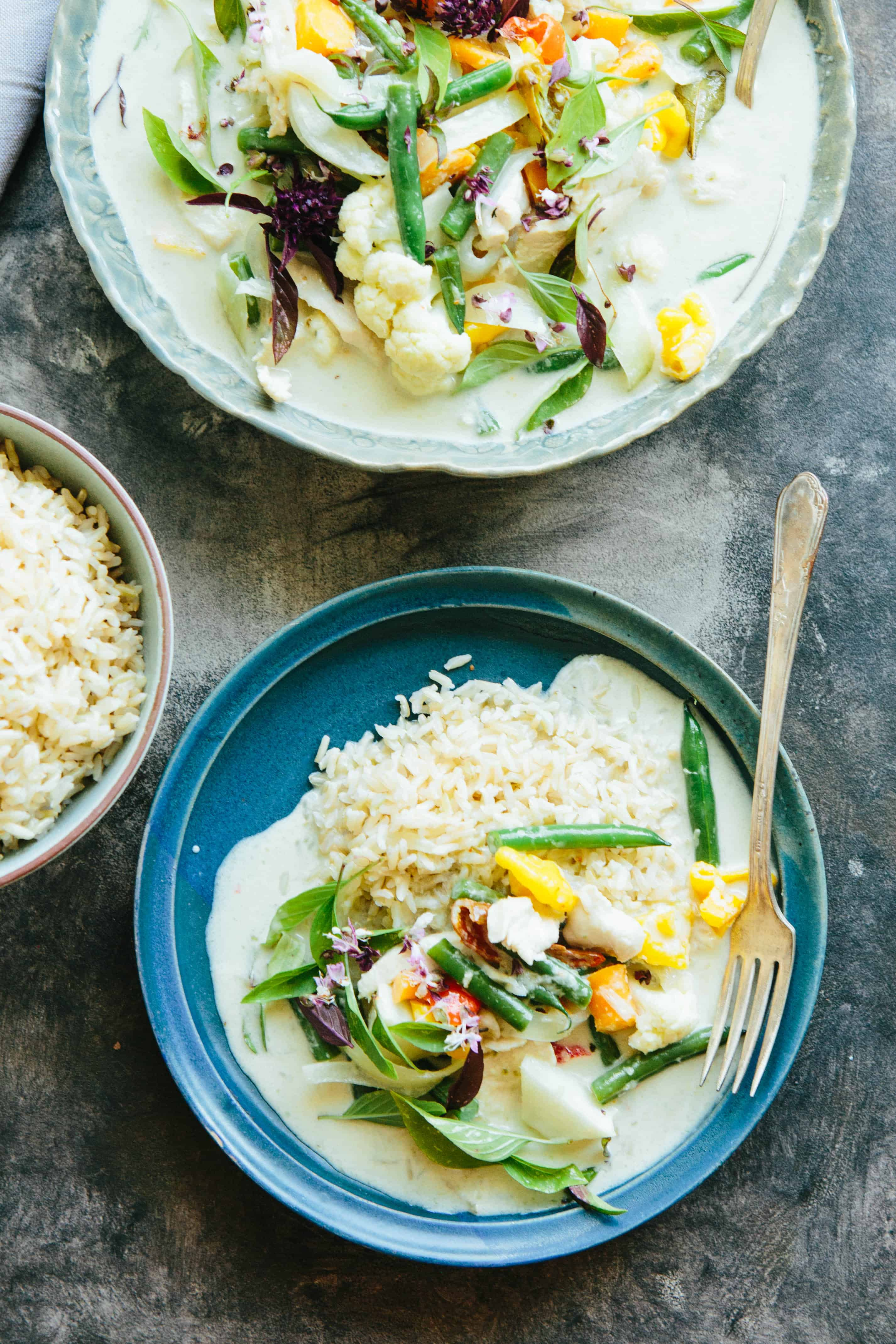A blue dinner plate with white rice and Thai green curry.