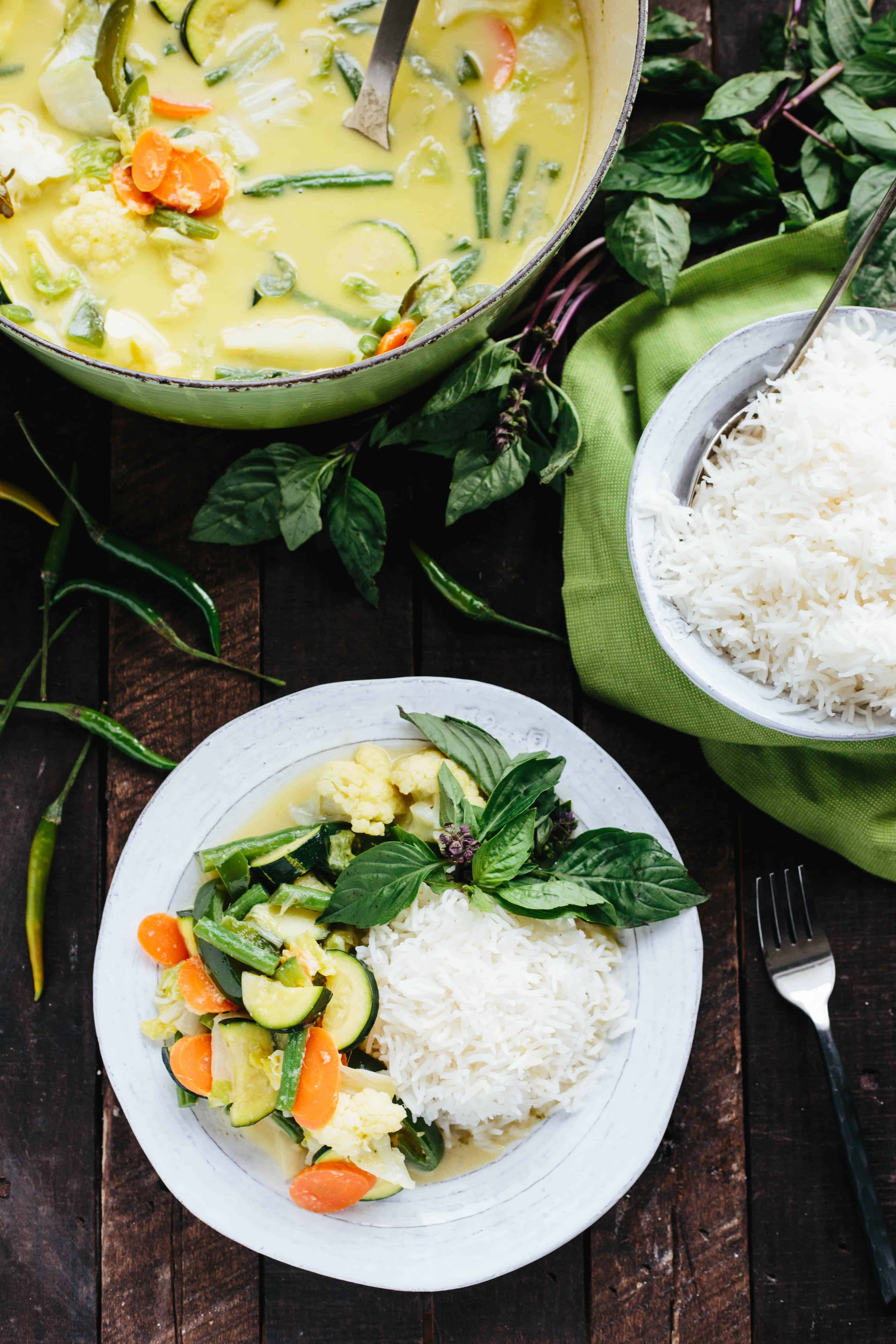 A table set with a large pot of curry, a bowl of rice, and a large helping of both on a white dinner plate.