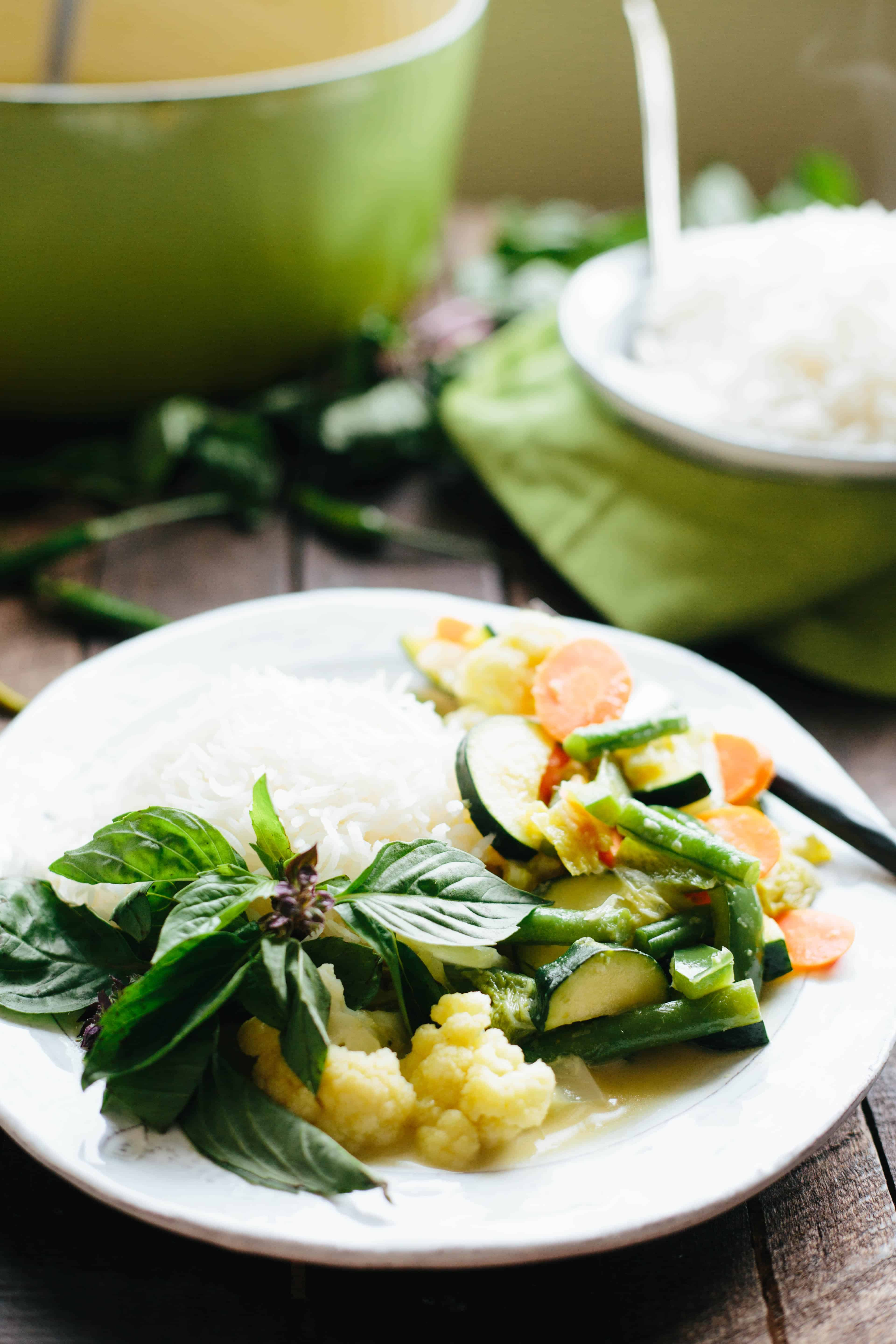 Close up shot of a white dinner plate filled with white rice and Thai green curry.