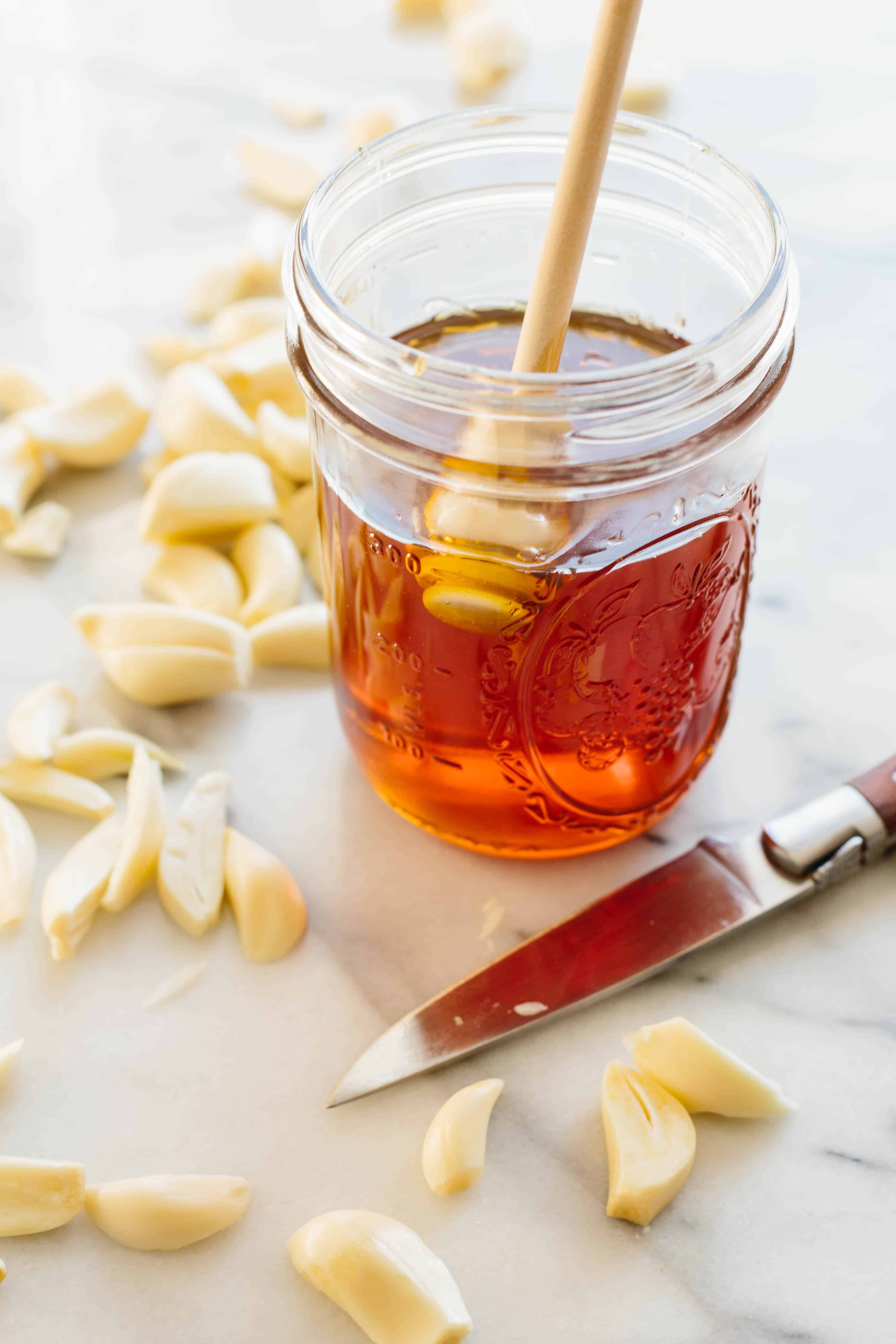 Close up of a glass pint jar of honey surrounded by peeled garlic cloves.