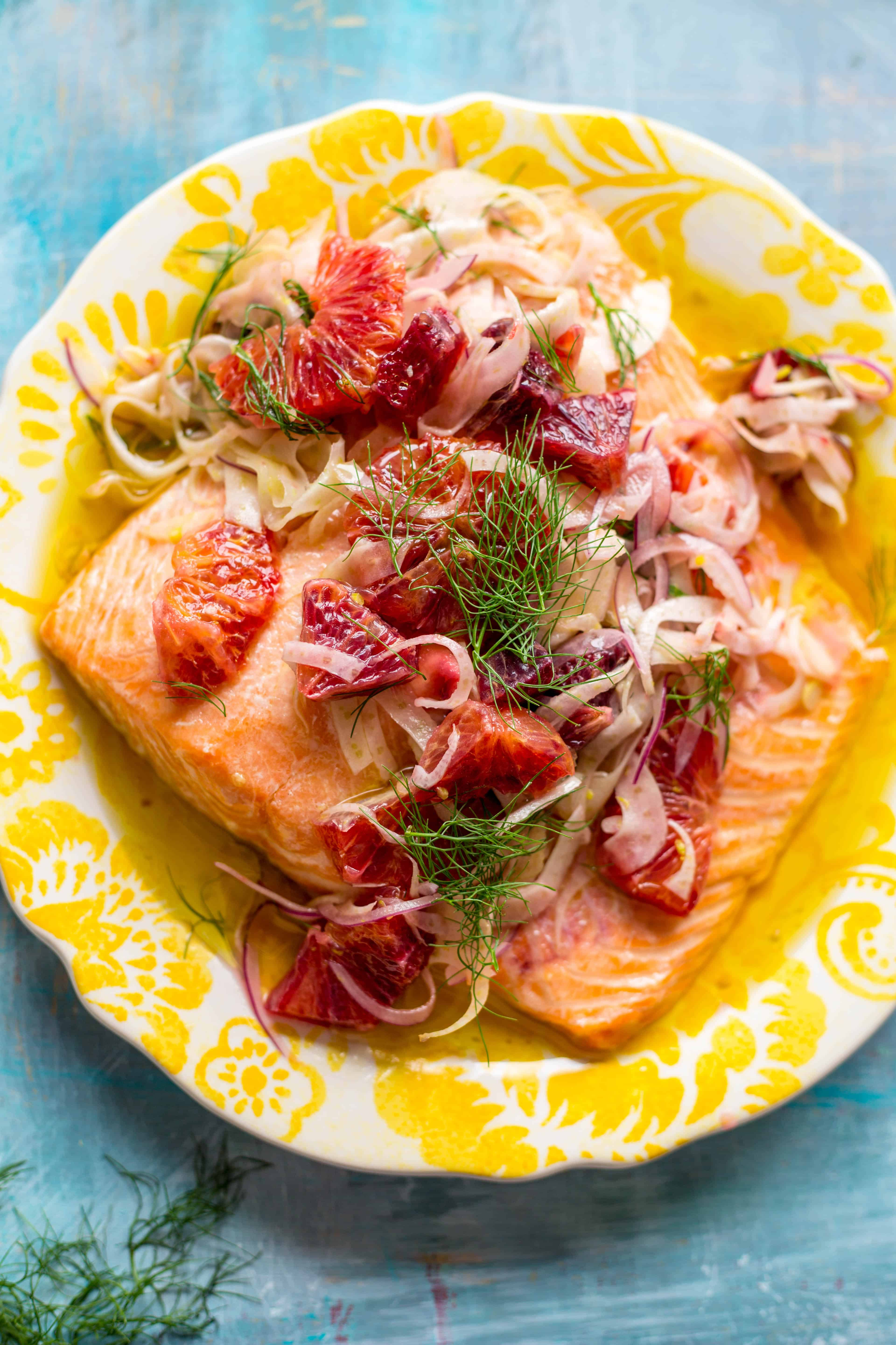 Top view of a yellow plate with a salmon fillet covered in fresh herbs and sliced citrus.