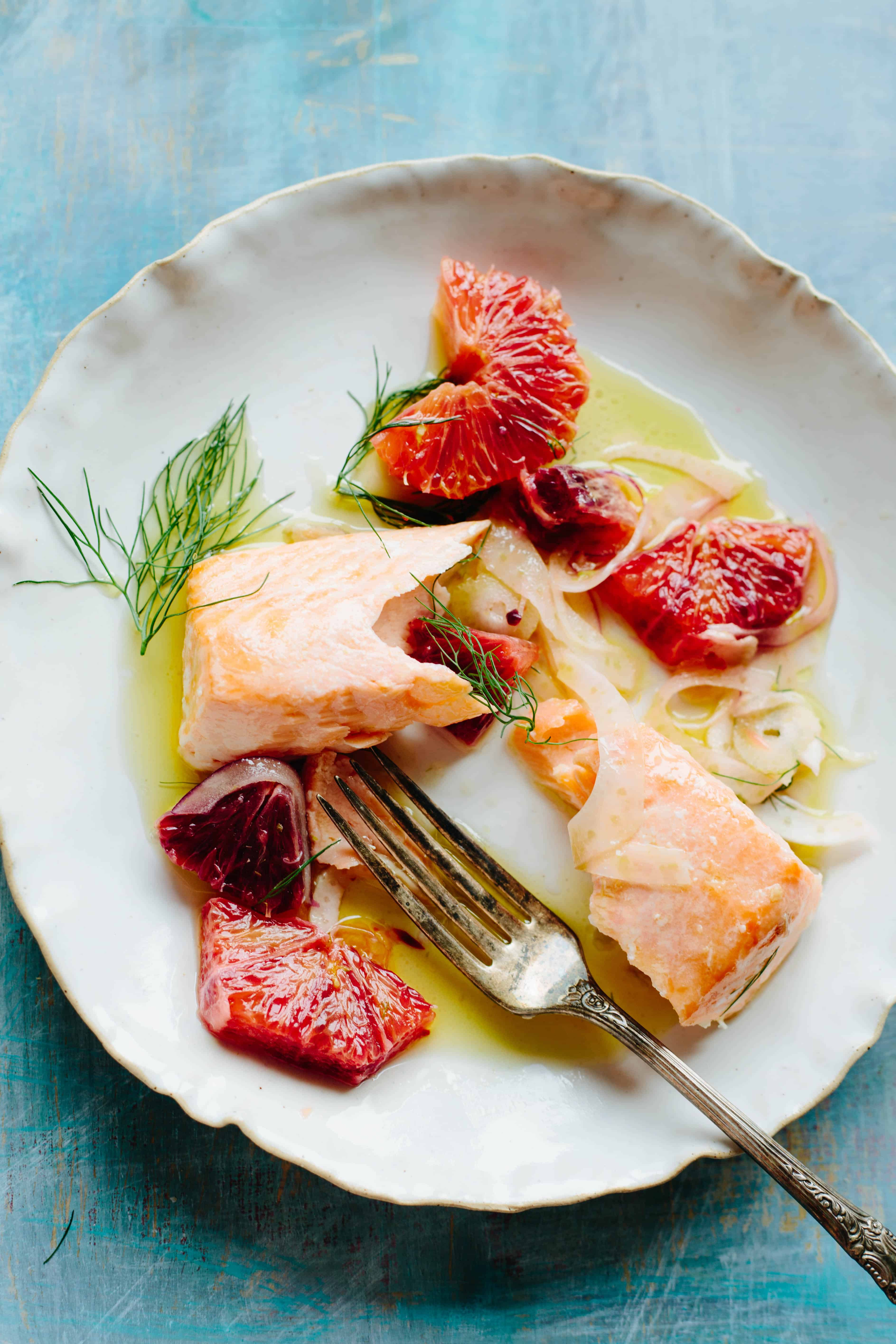 Top view of a salmon fillet flaked in two surrounded by citrus slices, dill, and oil.