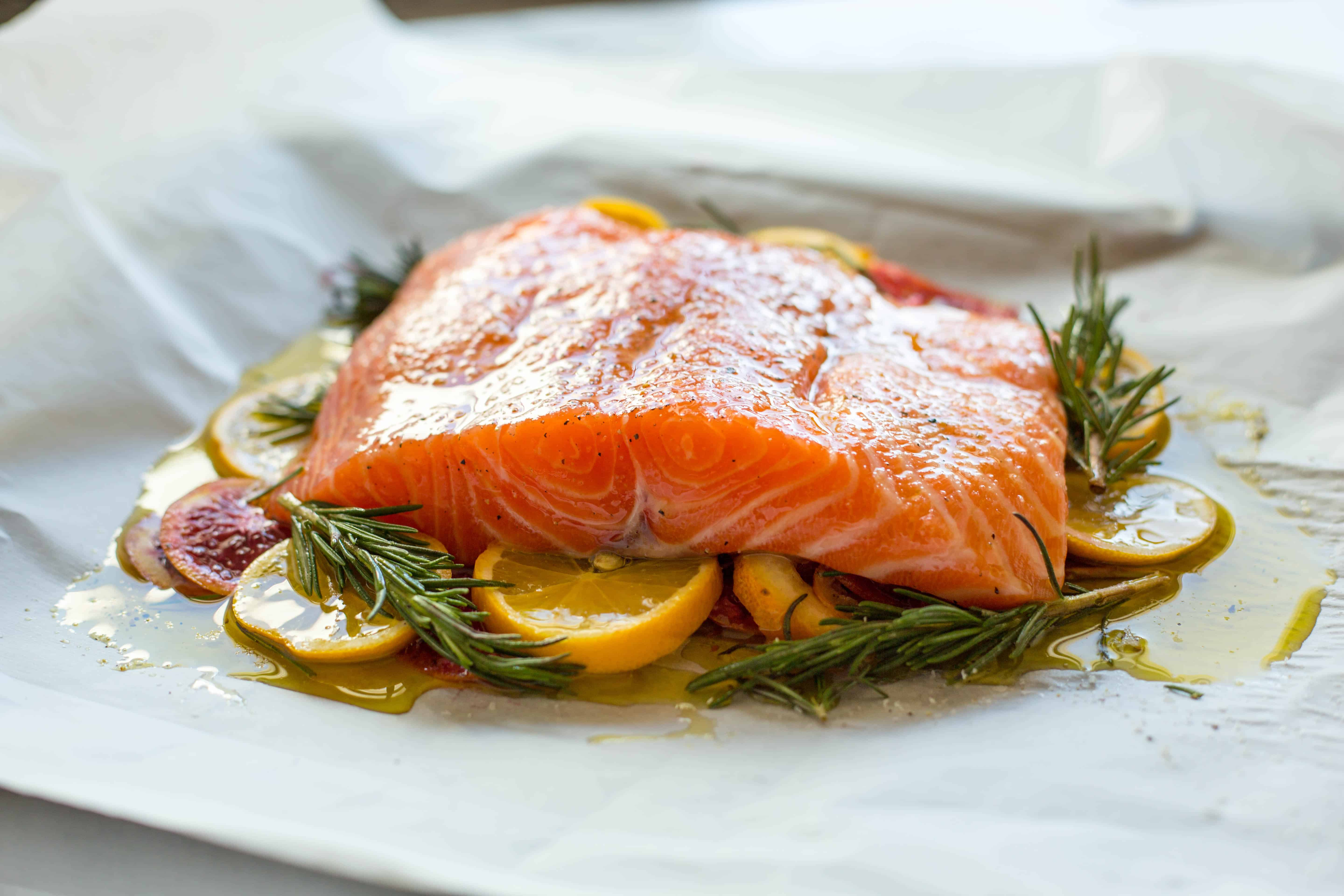 A salmon fillet on a bed of citrus and herbs ready to be wrapped in a parchment pocket.