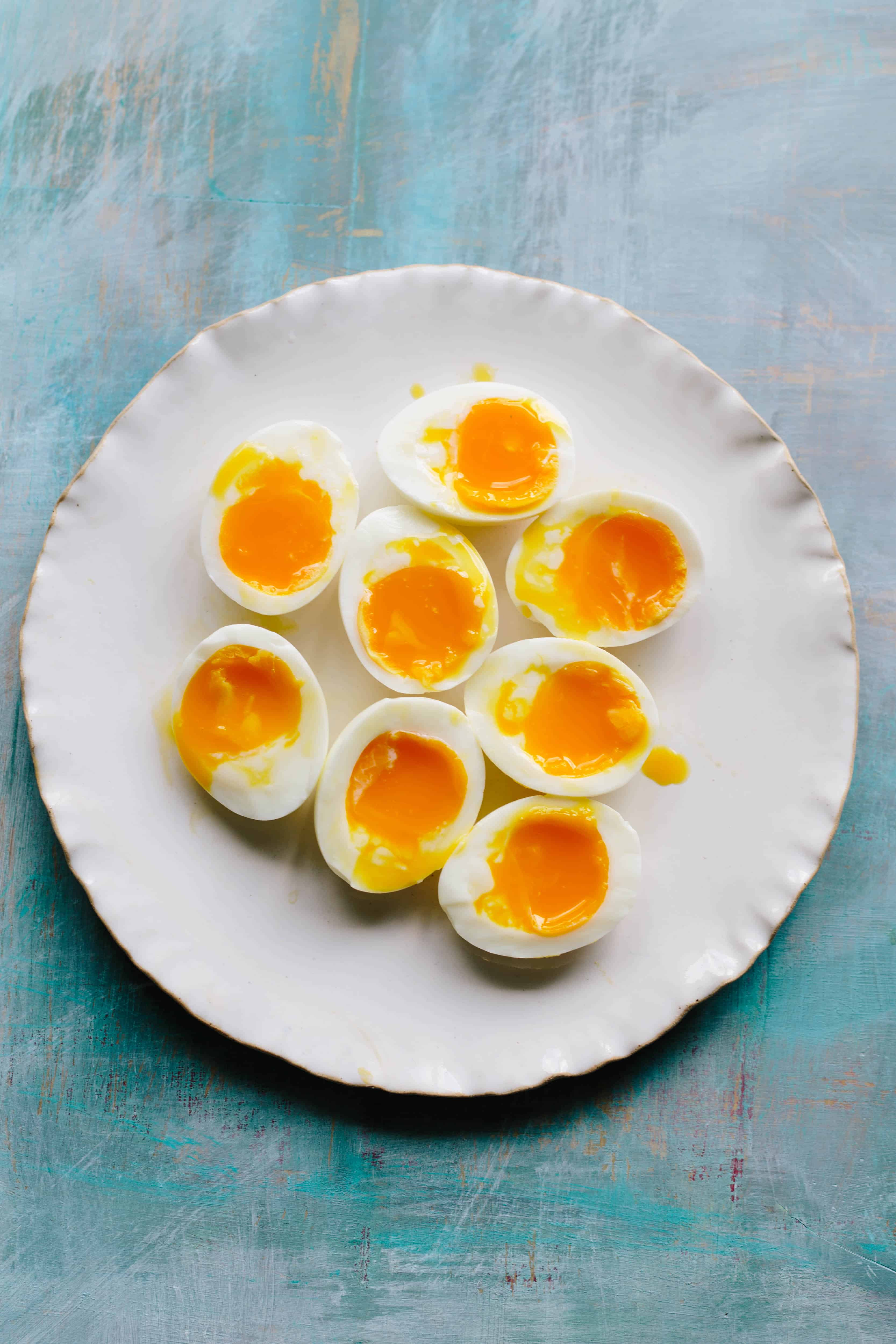 A white dinner plate with eight soft boiled egg halves.