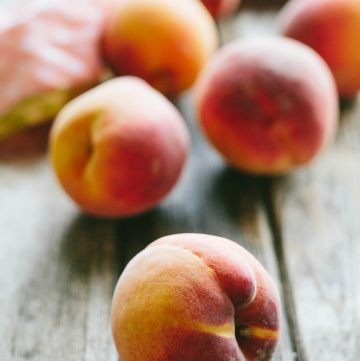 Beautiful whole peaches on a wooden table.