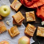 Square slices of almond apple shortbread spread on a table with whole apples mixed in.