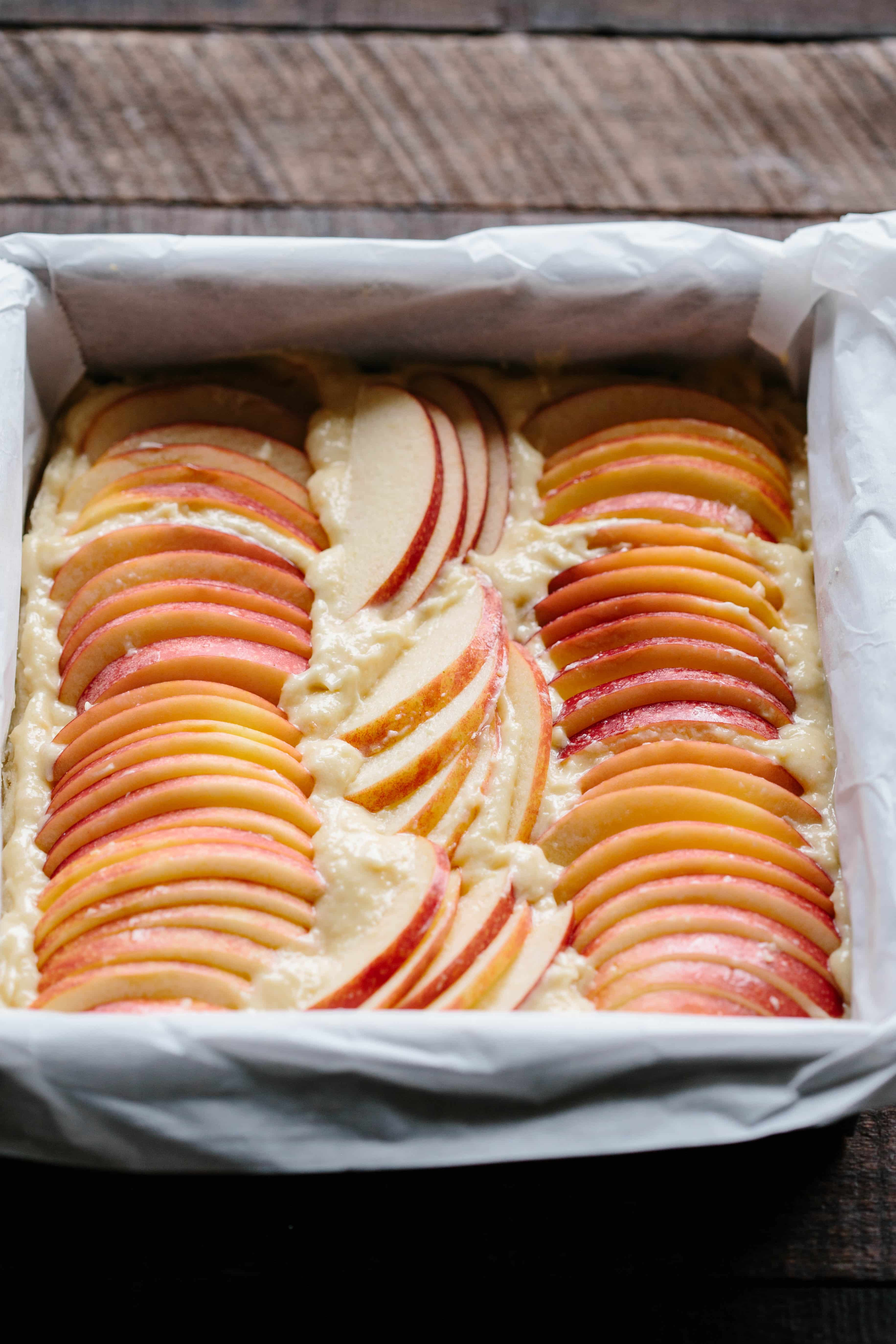 Thinly sliced apples lines up in a square baking pan of shortbread batter.