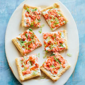 Six square pieces of smoked salmon puff pastry tart on a serving platter.