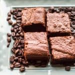 Espresso brownie squares on a tray surrounded by whole coffee beans.