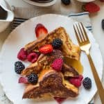 Three slices of stuffed French toast with fresh berries on a white plate.