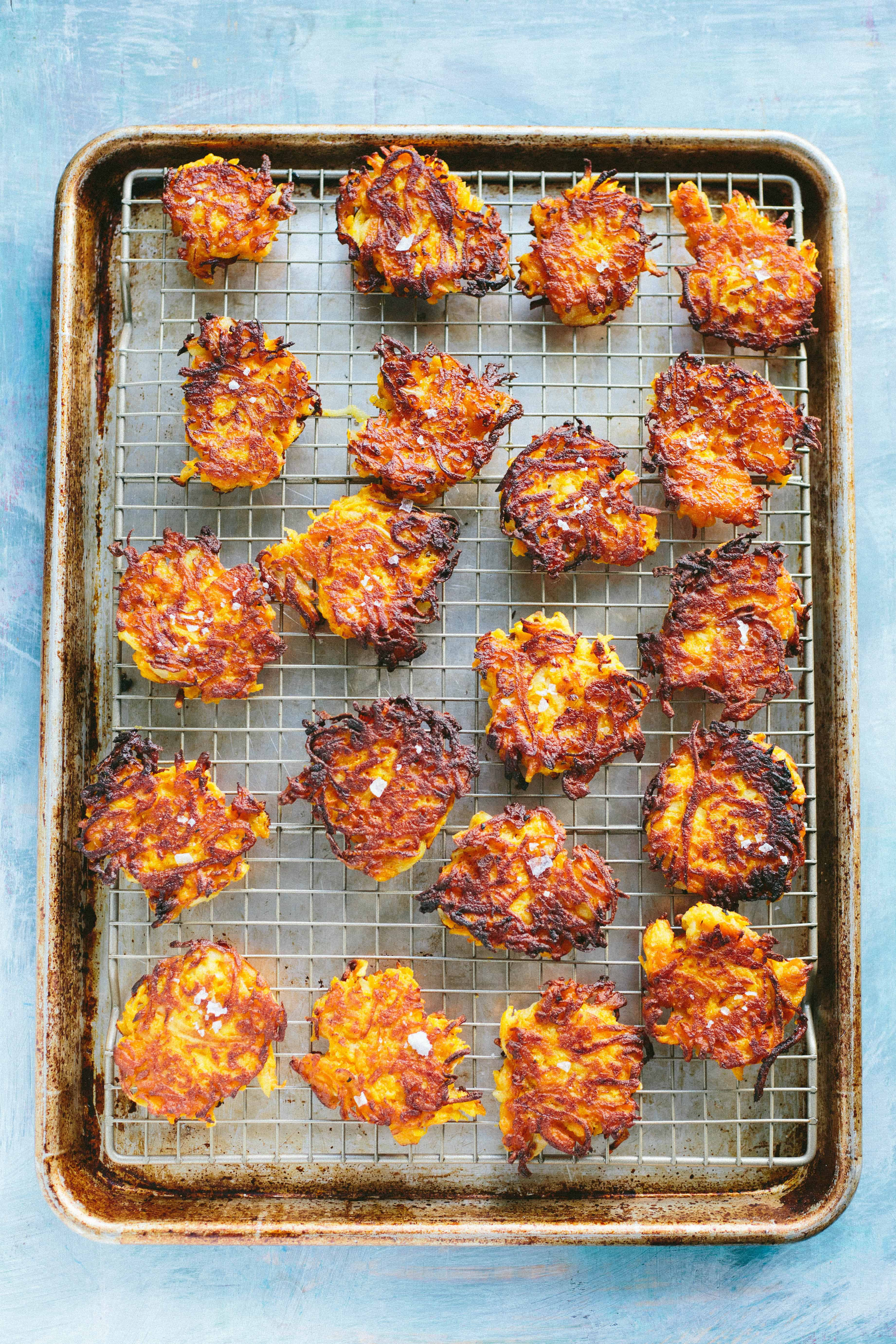 Butternut squash fritters draining on a metal rack over a baking sheet.