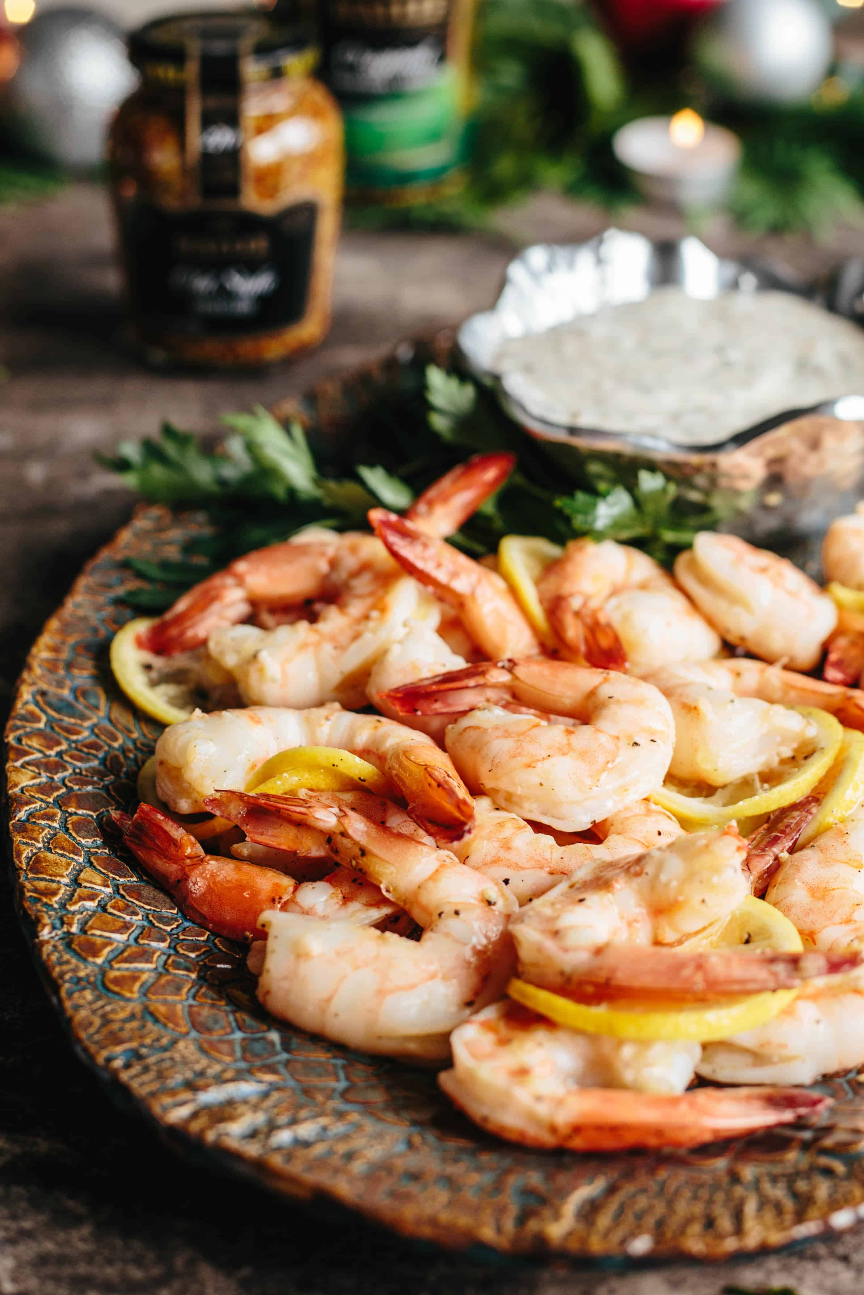 Close up of roasted shrimp mixed with thin slices of lemon on a platter.