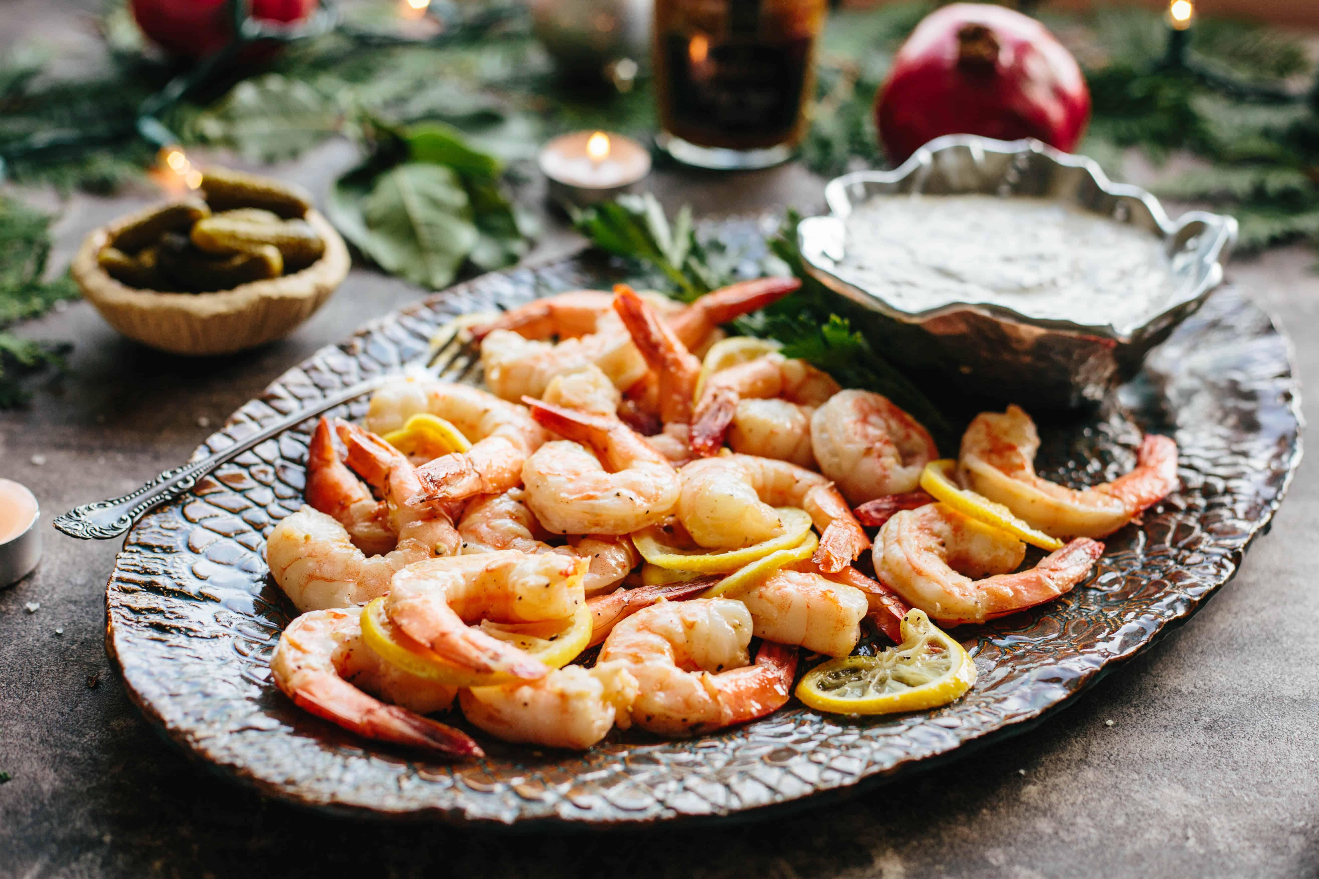 Roasted shrimp and sliced lemon on a platter.