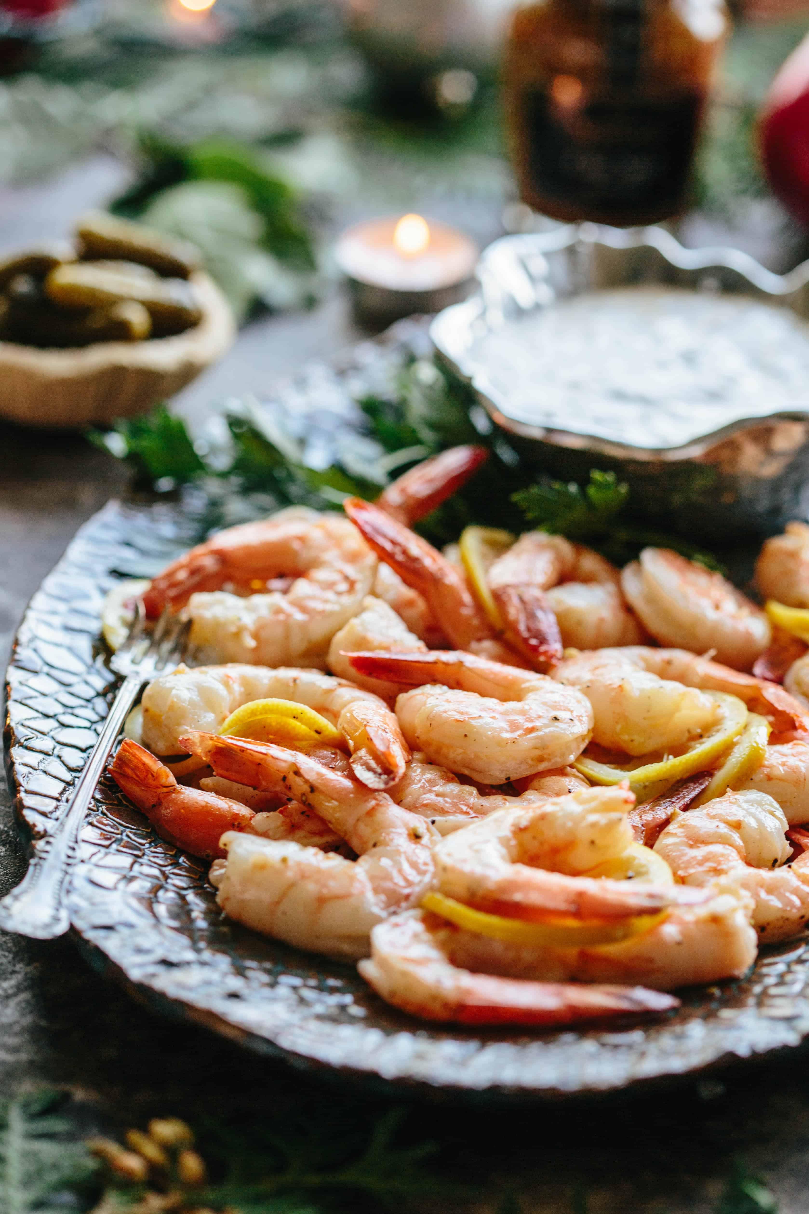 Close up of roasted shrimp and lemon on a serving platter.