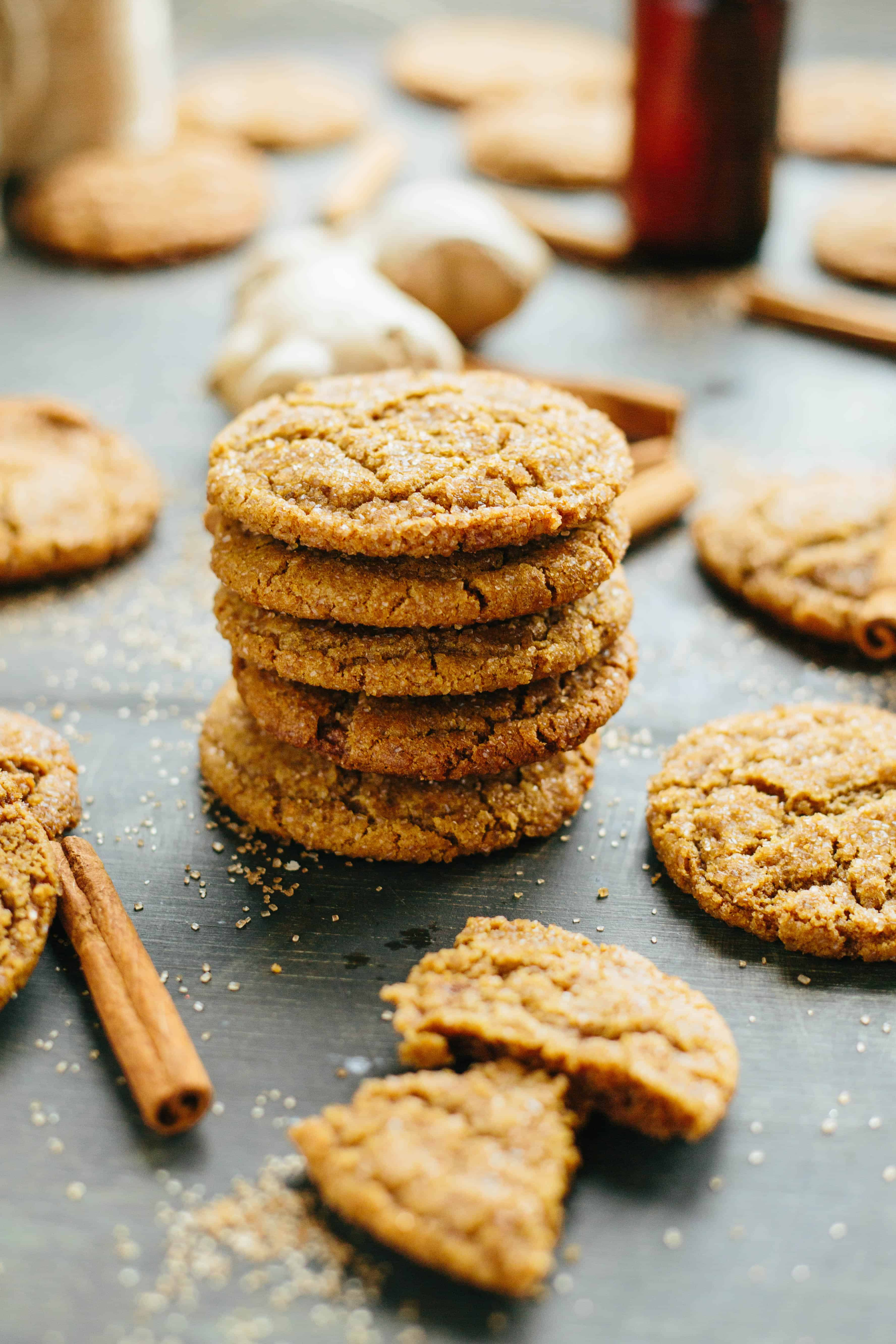 stack of Brown Butter Ginger Molasses Cookies with broken cookie and cinnamon sticks in the foreground
